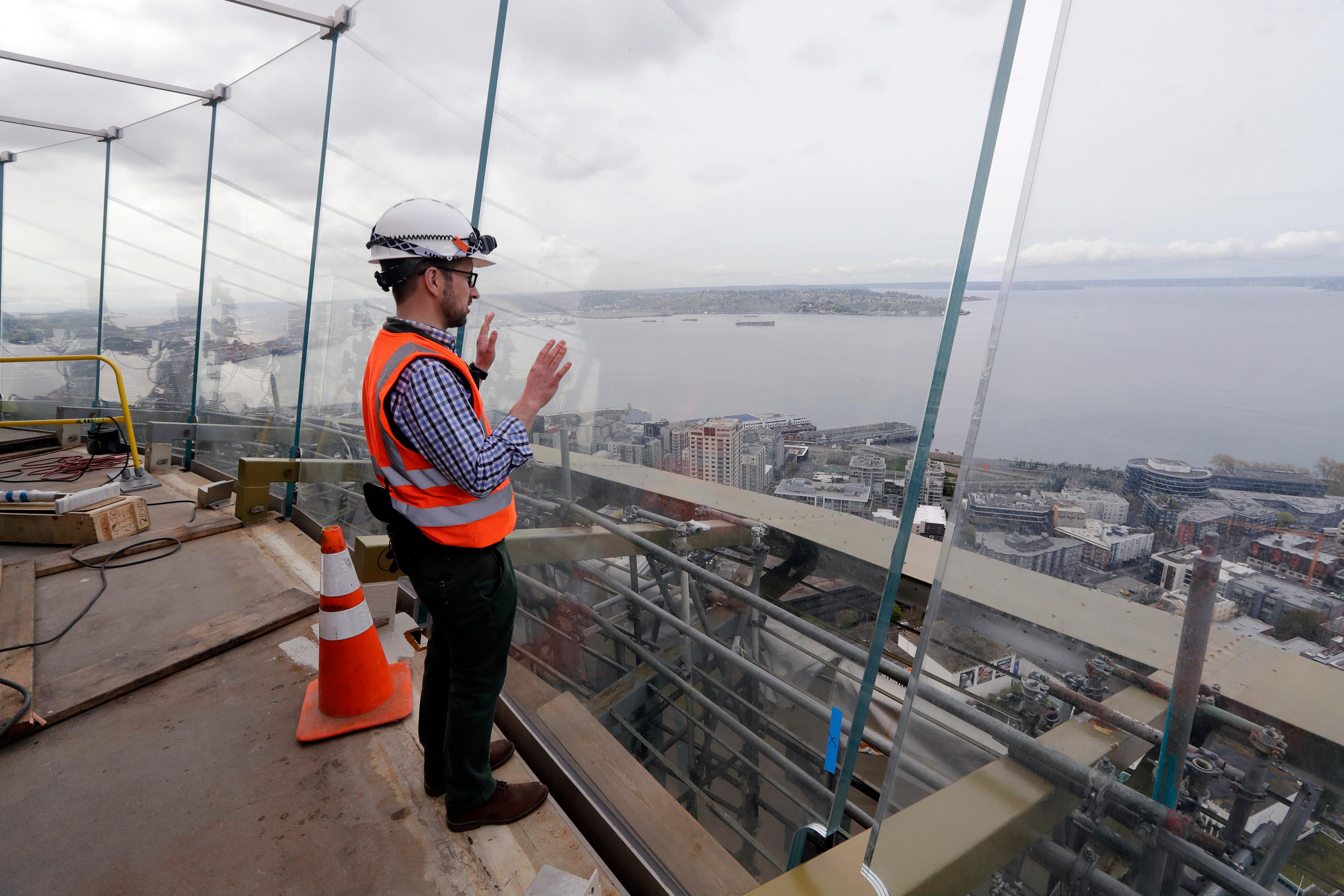 In this photo taken April 18, 2018, Space Needle facilities and construction superintendent Matt Waffle looks out over Elliott Bay through newly-installed glass panels atop the Space Needle in Seattle. The family-owned landmark is set to unveil the biggest renovation in its 56 year history next month, a $100 million investment in a single year of construction that transformed the structure's top viewing level some 500-feet above ground. The preservation and renovation project included the installation of floor-to-ceiling glass on the viewing deck, updated the structure's physical systems and adds a glass floor to the rotating restaurant. (AP Photo/Elaine Thompson)