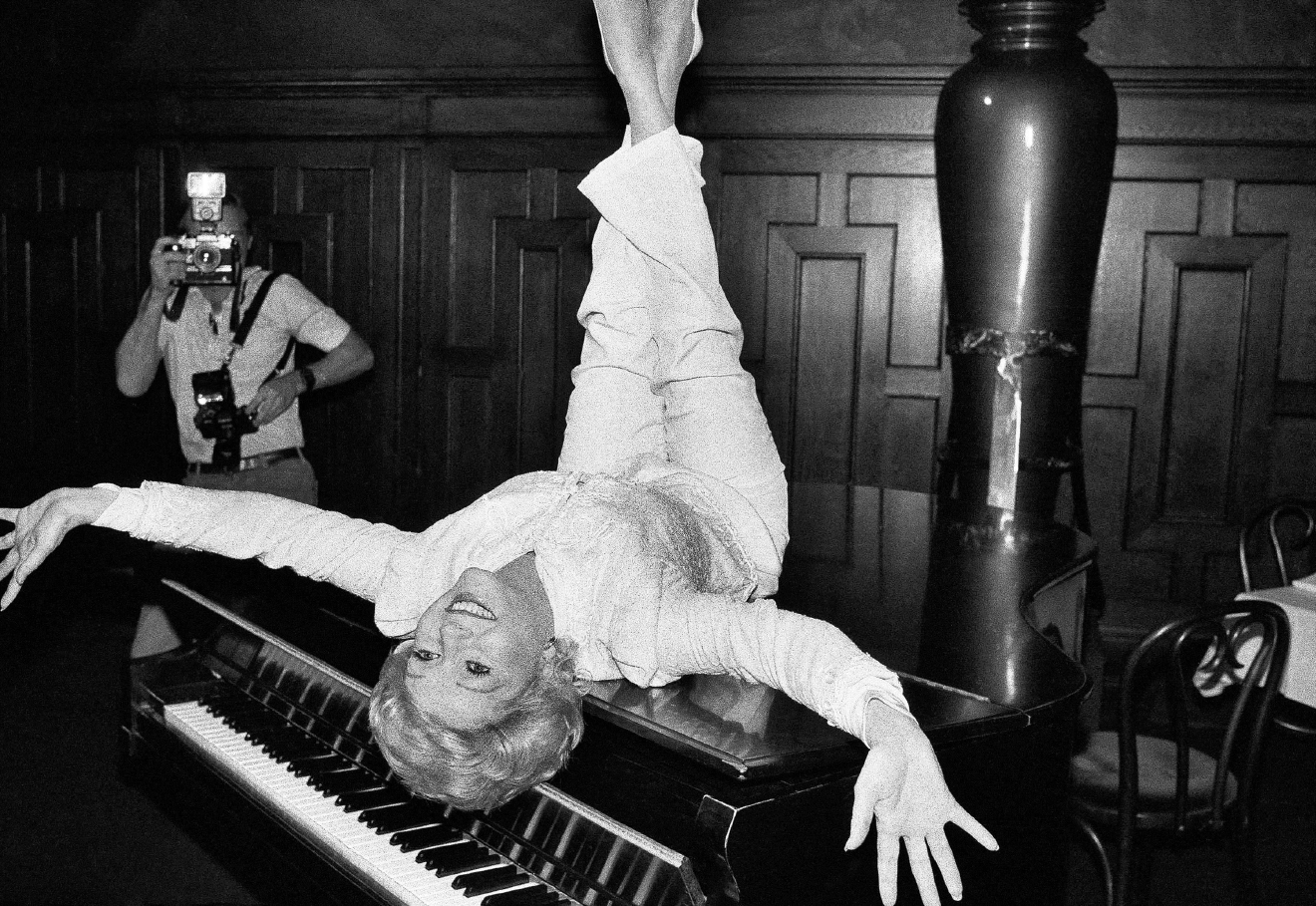 Actress Debbie Reynolds poses on a grand piano at a New York restaurant, Tuesday, Sept. 8, 1982 as she promotes the revival of the hit musical ?The Unsinkable Molly Brown? which will end up on Broadway next summer after an extensive national tour. Debbie played the title role in the Hollywood version of the play. (AP Photo/Marty Lederhandler)