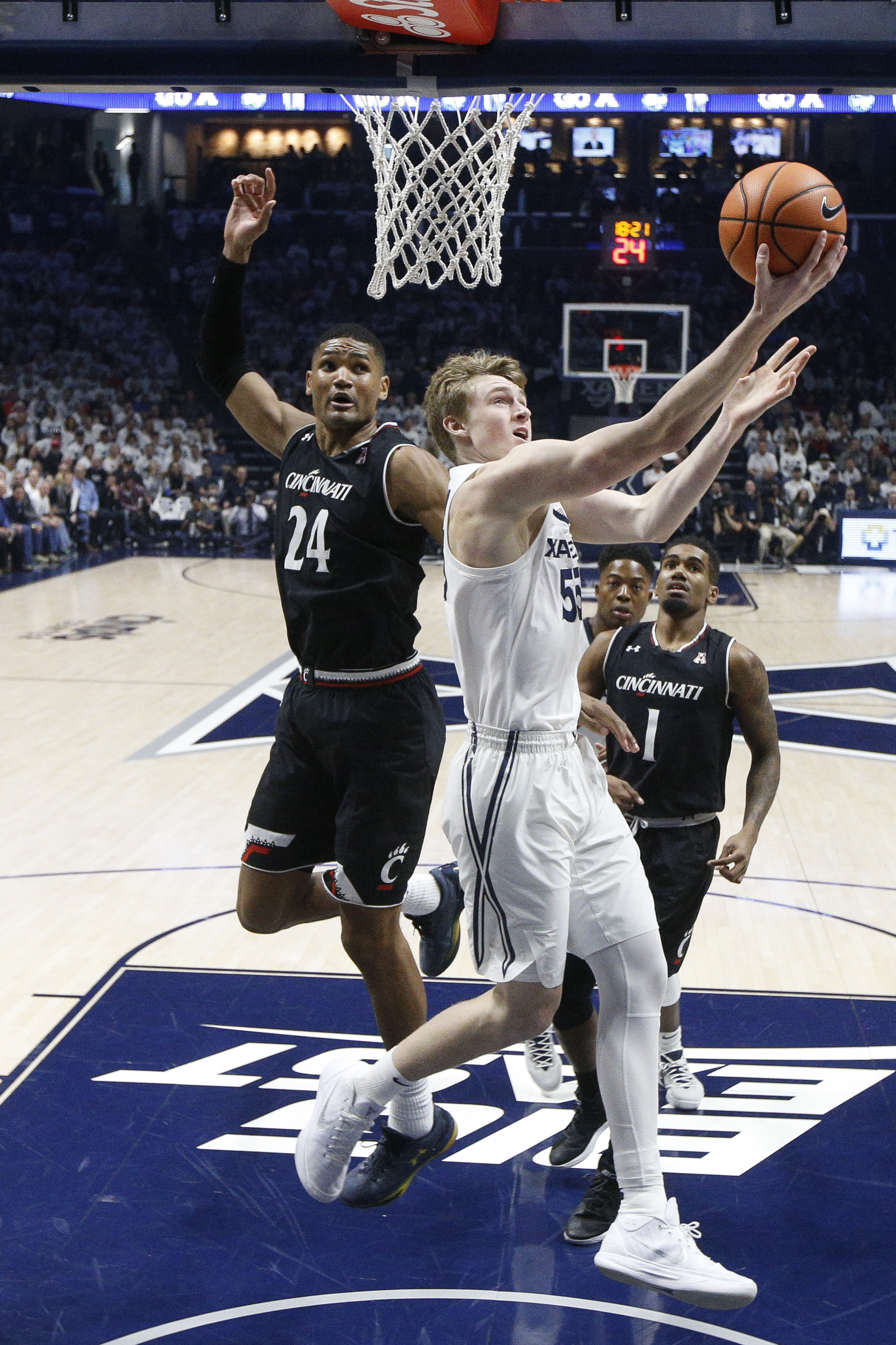 Xavier's J.P. Macura (55) shoots against Cincinnati's Kyle Washington (24) in the first half of an NCAA college basketball game, Saturday, Dec. 2, 2017, in Cincinnati. (AP Photo/John Minchillo)