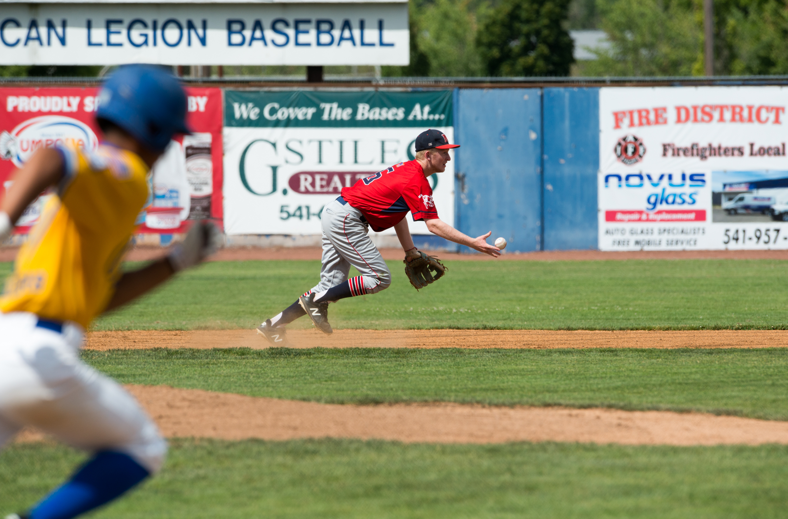 Medford shortstop Zac Ankeny flips the ball toward second after fielding a grounder by Corvallis' Azel Bumpus during Tuesday's game at Legion Field.