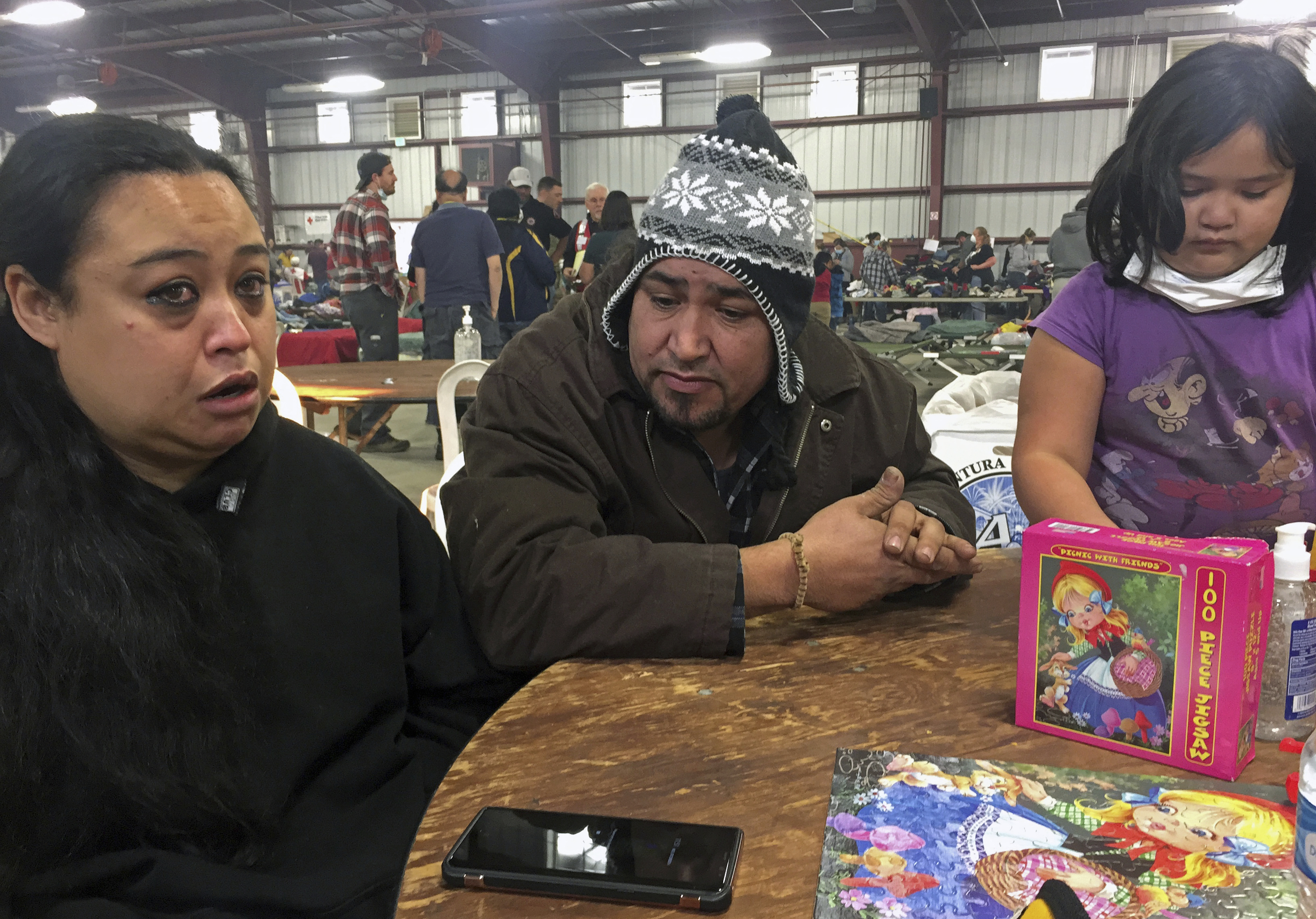 Wildfire survivors Marolyn Romero-Sim left, and Hugo Romero-Rodriguez, middle, and their 9-year-old daughter, Milagros, sit inside the evacuation center at the Ventura County Fairgrounds in Ventura, Calif. Their RV burned up with all their possessions in Ventura, Calif. Wind-driven fires have raced through California communities for the second time in two months, leaving hundreds of homes feared lost and uprooted tens of thousands of people. The most damaging fire is in Ventura County northwest of Los Angeles, where more than 100 square miles (259 sq. kilometers) and numerous homes have burned. (AP Photo/Amanda Lee Myers)