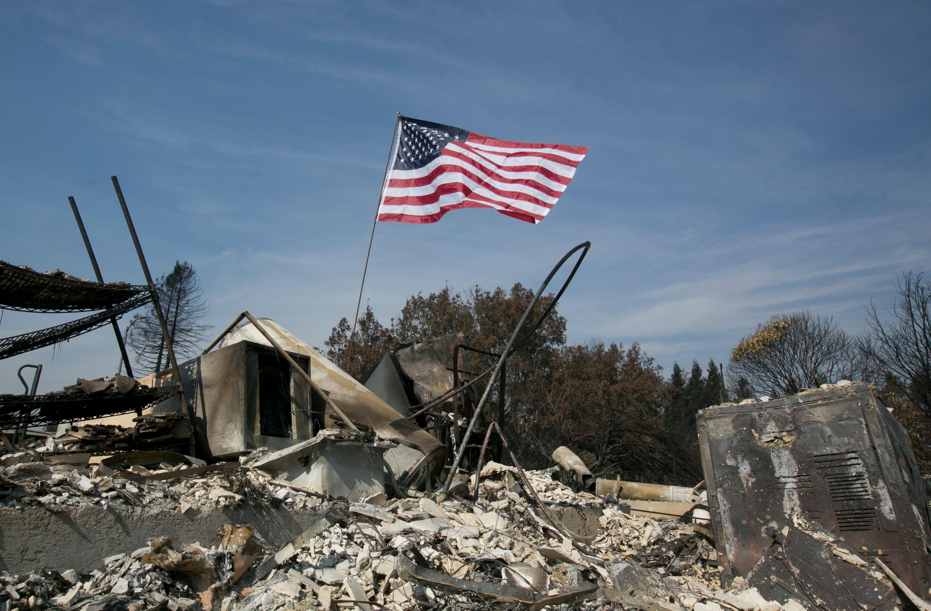 A United States flag flies over the charred remains of a house in the Coffey Park area of Santa Rosa, Calif., Monday, Oct. 16, 2017. (AP Photo/Rich Pedroncelli)