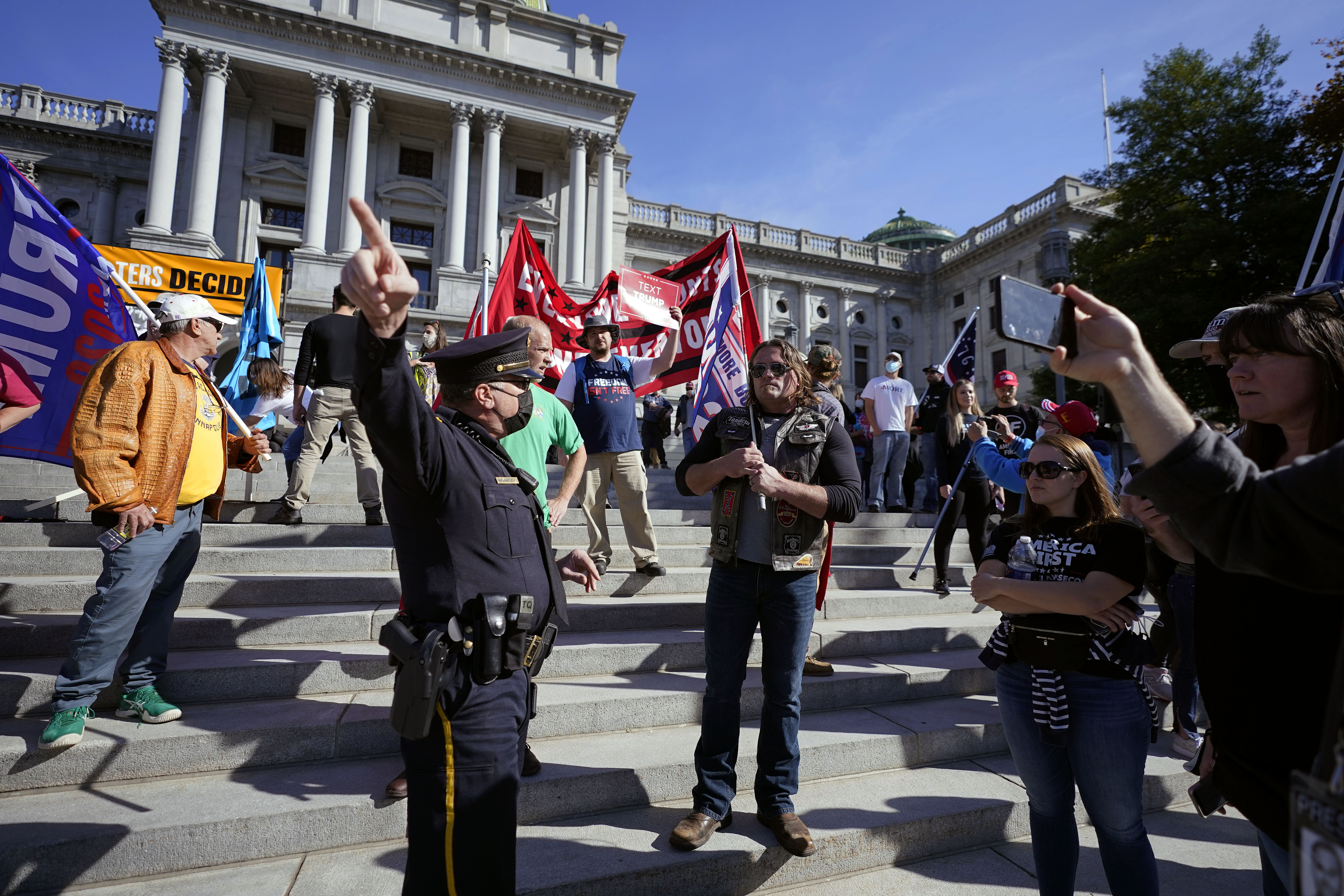 A police officer directs supporters of President Donald Trump away from the Pennsylvania State Capitol Plaza where they did not have a permit to demonstrate, Saturday, Nov. 7, 2020, in Harrisburg, Pa. A permit had been granted to an opposing group. (AP Photo/Julio Cortez)