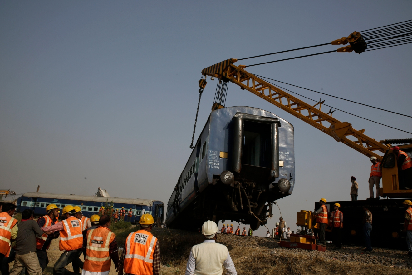 Rescuers lift one of the 14 coaches of an overnight passenger train that rolled off the track near Pukhrayan village Kanpur Dehat district, Uttar Pradesh state, India, Sunday, Nov. 20, 2016. Dozens were killed and dozens more were injured in the accident. (AP Photo/Rajesh Kumar Singh)
