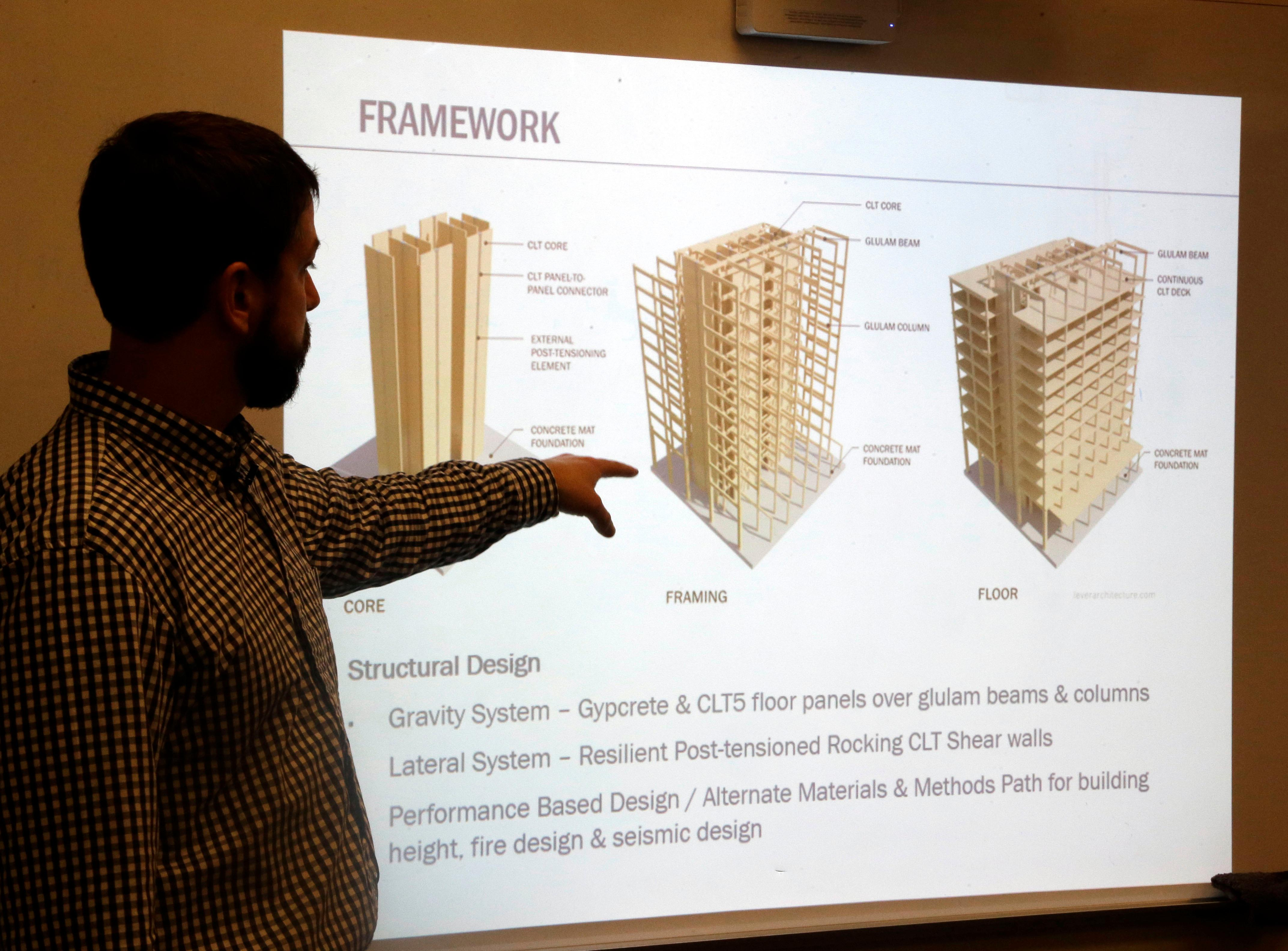 FILE--In this Nov. 15, 2016, file photo, structural engineer Eric McDonnell shows diagrams of skyscraper construction using cross-laminated timber, or CLT, at Portland State University in Portland, Ore. City officials in Portland have approved a construction permit for the first all-wood high-rise building in the nation. The building uses the new technology called cross-laminated timber that tests have shown can withstand the worst earthquakes. Developers worked with scientists at Portland State University and Oregon State University to prove through testing that the materials meet all building and fire safety codes. (AP Photo/Don Ryan, file)