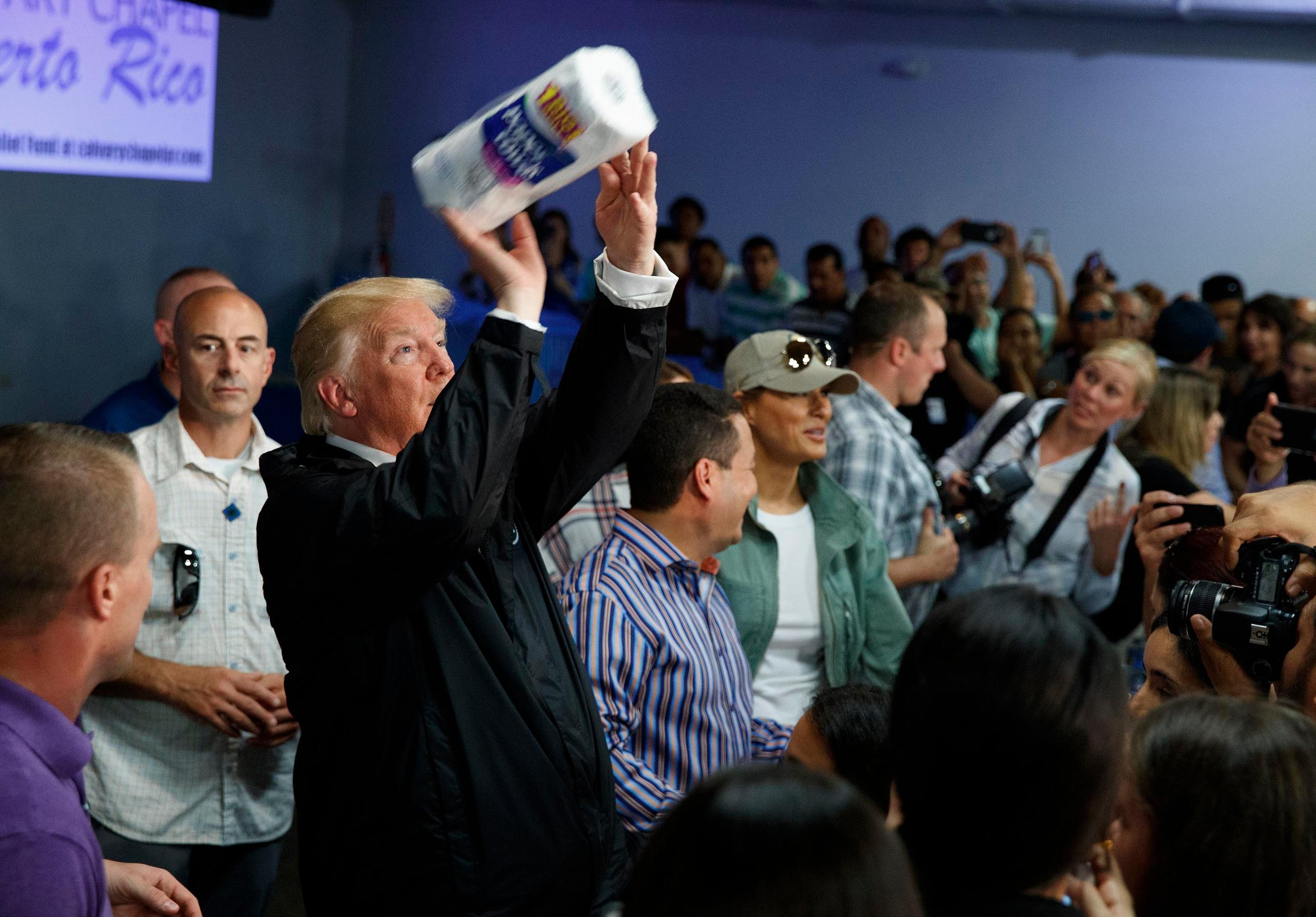President Donald Trump tosses paper towels into a crowd as he hands out supplies at Calvary Chapel, Tuesday, Oct. 3, 2017, in Guaynabo, Puerto Rico. Trump is in Puerto Rico to survey hurricane damage. (AP Photo/Evan Vucci, File)