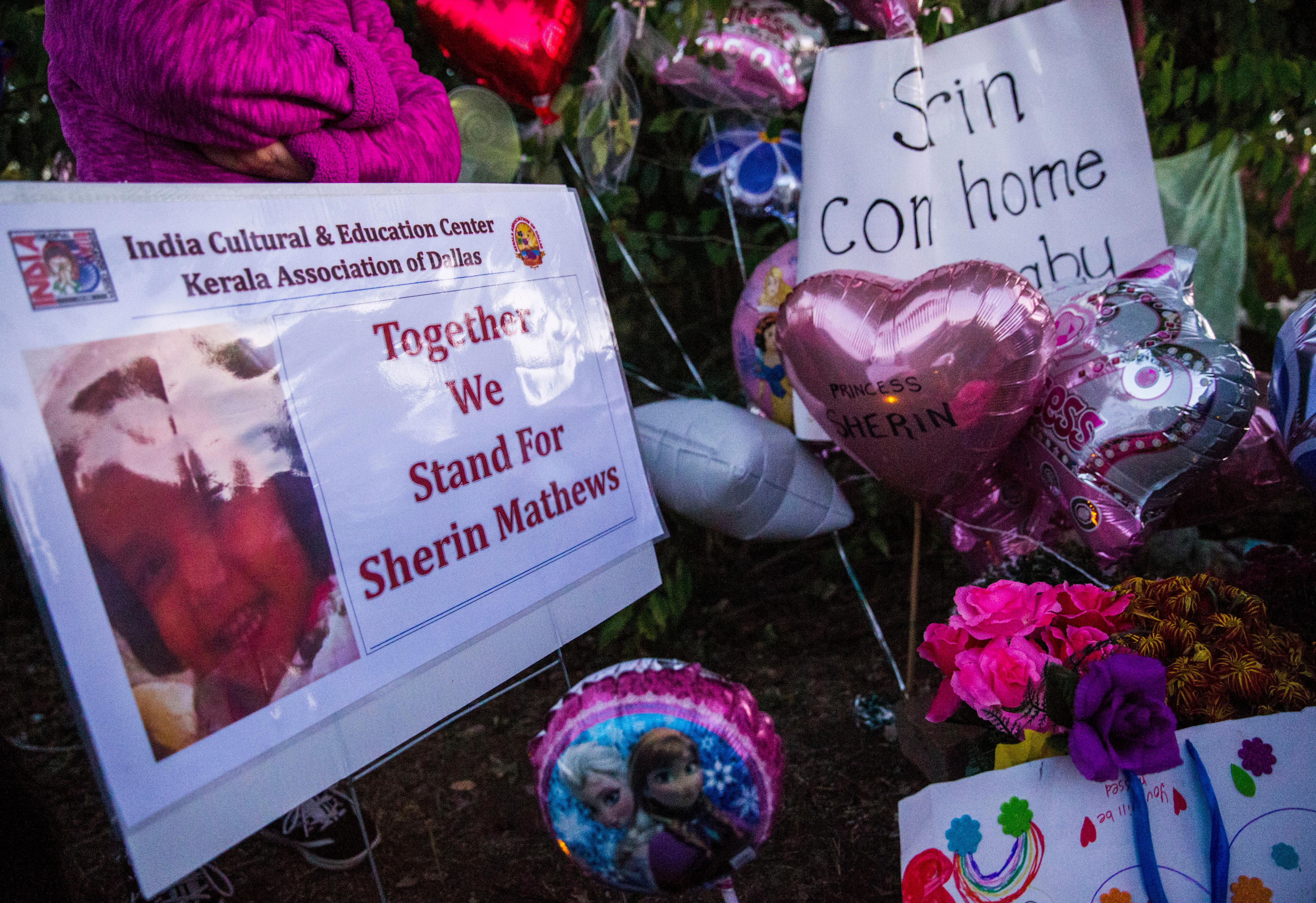 In this Sunday, Oct. 22, 2017 photo, signs, flowers and other items collect at a memorial for missing 3-year-old Sherin Mathews at a tree behind her home in Richardson, Texas. (Ashley Landis/The Dallas Morning News via AP)