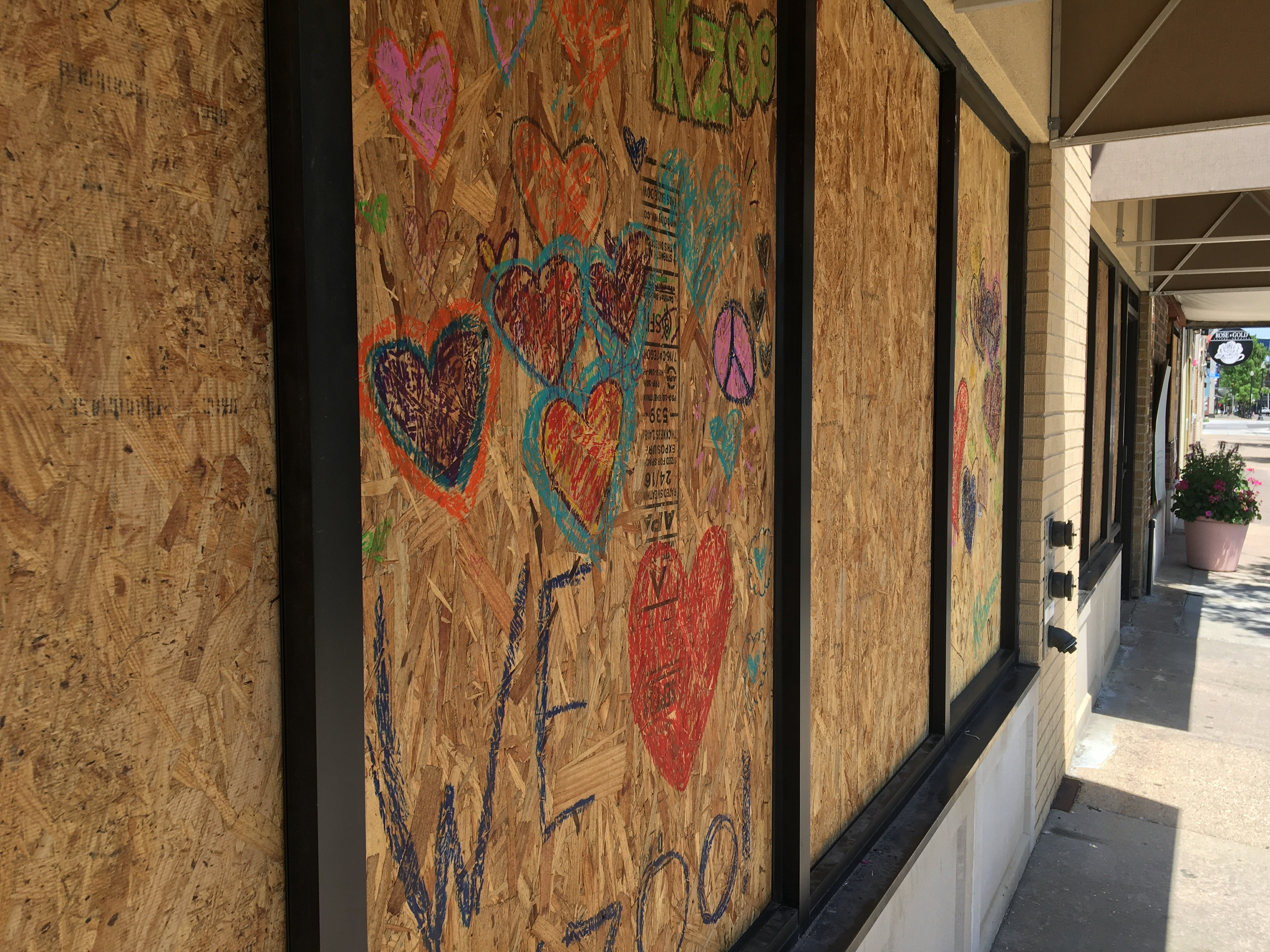 A couple business owners get creative with the boards being used to cover, and protect windows and doors Tuesday, June 2, 2020, as Kalamazoo prepares for an expected second night of looting and vandalism. (WWMT/Manny Revilla)