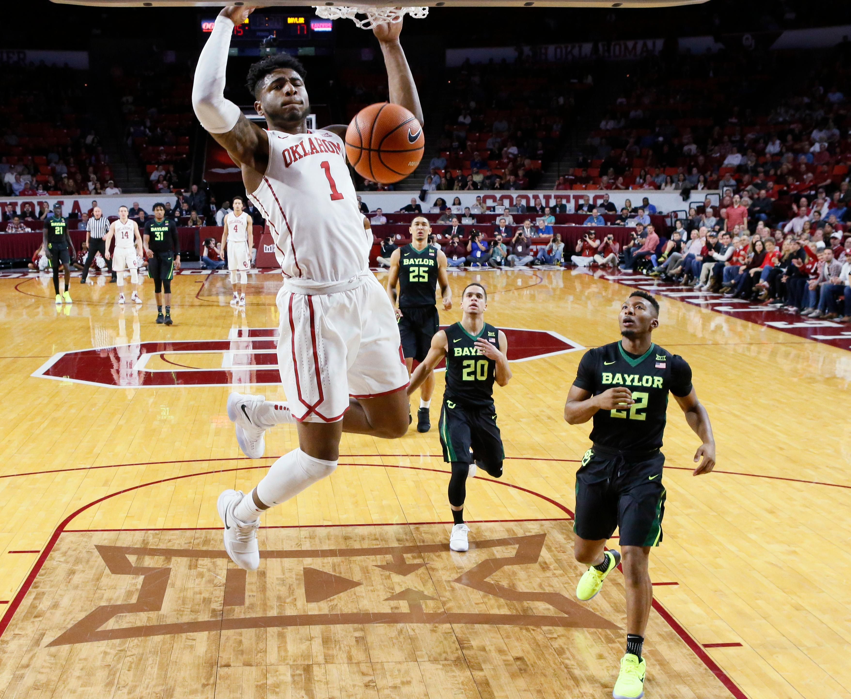 Oklahoma guard Rashard Odomes (1) dunks in front of Baylor guard Manu Lecomte (20) and guard King McClure (22) during the first half of an NCAA college basketball game in Norman, Okla., Tuesday, Jan. 30, 2018. (AP Photo/Sue Ogrocki)