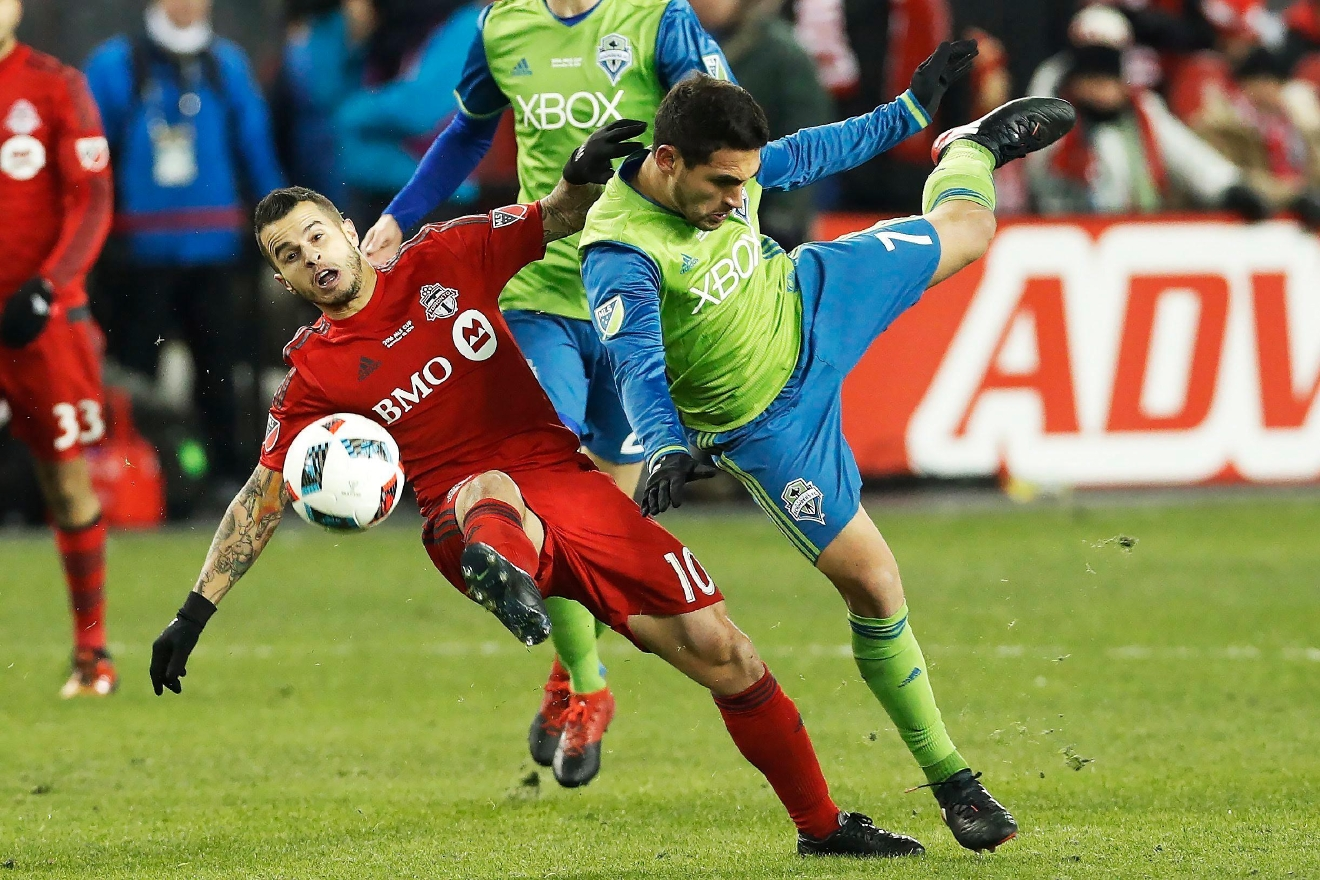 Toronto FC forward Sebastian Giovinco (10) and Seattle Sounders midfielder Cristian Roldan (7) battle for the ball during second-half MLS Cup final soccer action in Toronto, Saturday, Dec. 10, 2016. (Mark Blinch/The Canadian Press via AP)