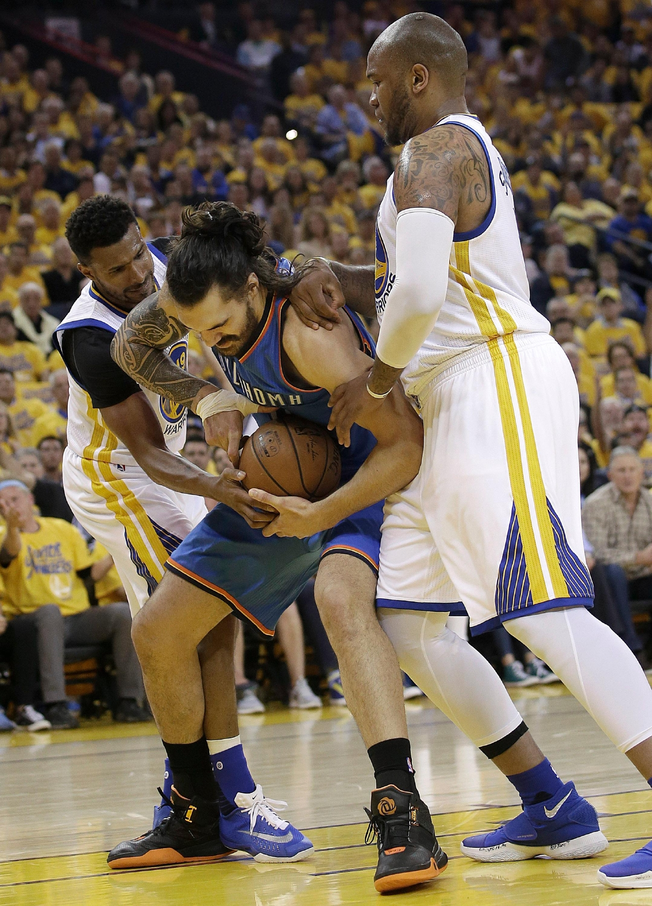 Oklahoma City Thunder center Steven Adams, center, holds onto the ball as he is defended by Golden State Warriors guard Leandro Barbosa, left, and forward Marreese Speights during the first half of Game 5 of the NBA basketball Western Conference finals in Oakland, Calif., Thursday, May 26, 2016. (AP Photo/Marcio Jose Sanchez)