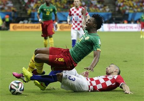Croatia's Danijel Pranjic, right, slides underneath Cameroon's Benjamin Moukandjo during the group A World Cup soccer match between Cameroon and Croatia at the Arena da Amazonia in Manaus, Brazil, Wednesday, June 18, 2014.