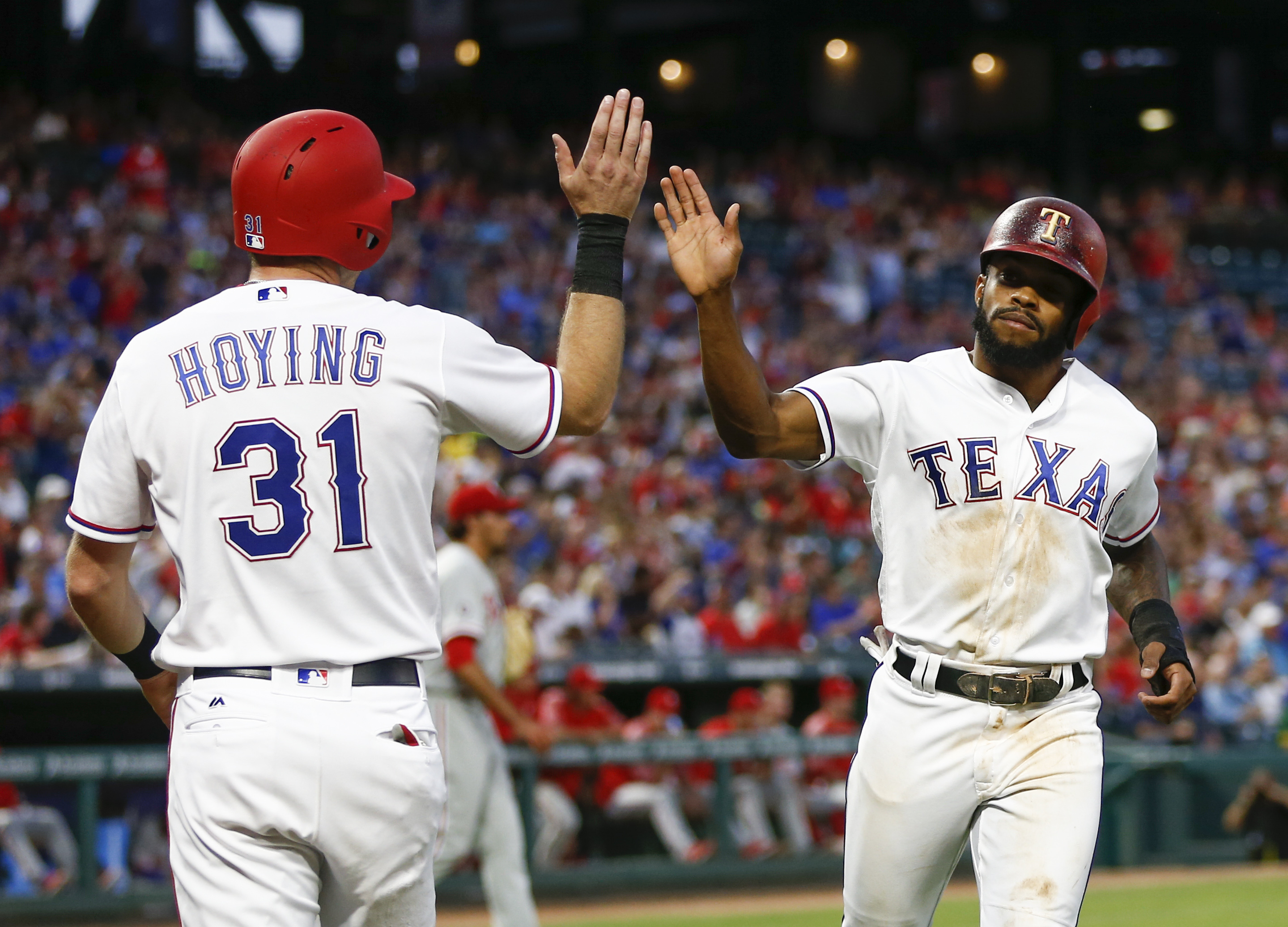 Texas Rangers' Delino DeShields, right, and Jared Hoying (13) celebrate scoring on a single by Shin-Soo Choo against the Philadelphia Phillies during the third inning of a baseball game, Wednesday, May 17, 2017, in Arlington, Texas. (AP Photo/Jim Cowsert)