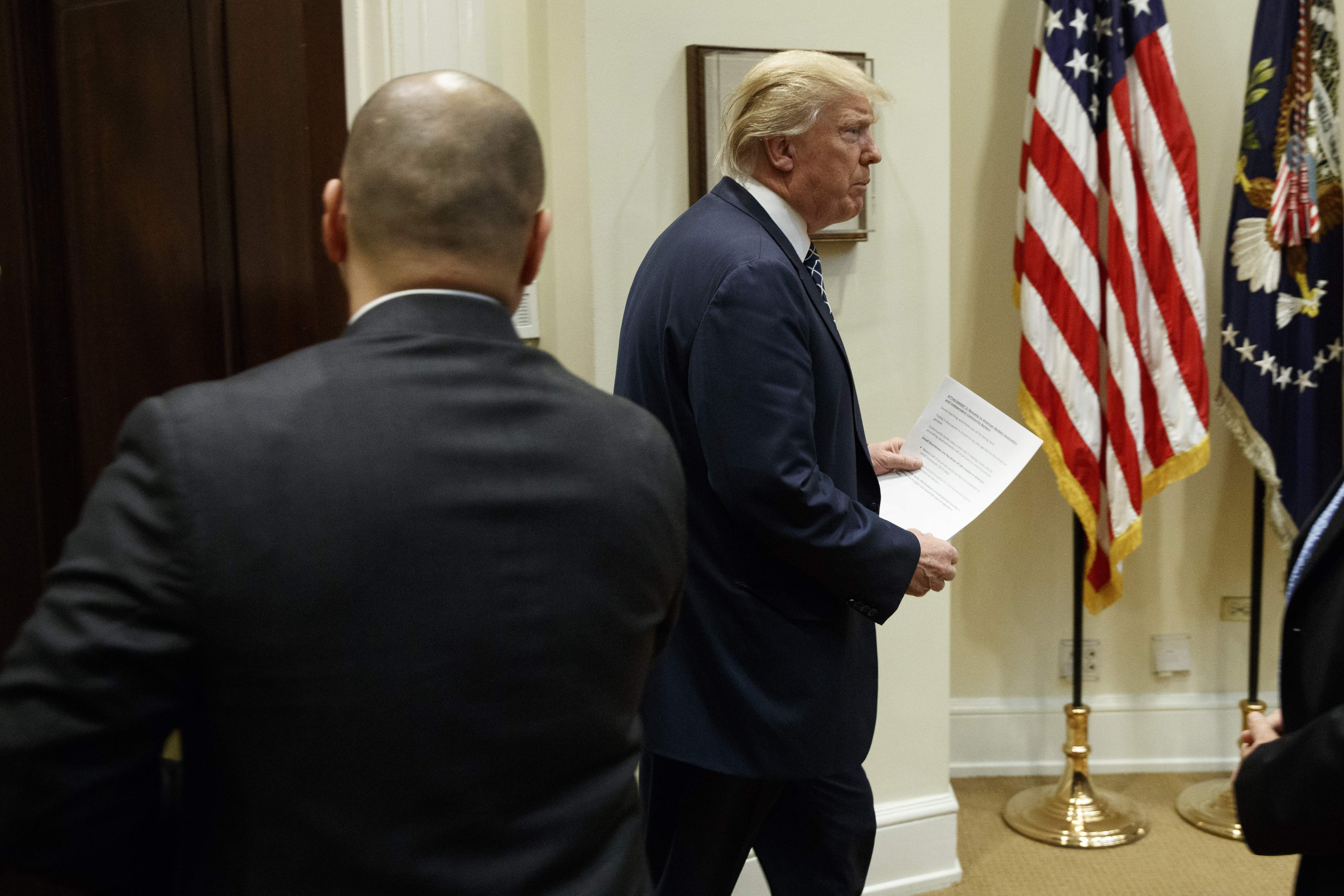 DAY 49 - In this March 9, 2017, file photo, President Donald Trump arrives in the Roosevelt Room of the White House in Washington, for a meeting with leaders from small community banks. (AP Photo/Evan Vucci, File)