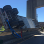 Truck crashes on exit ramp, trailer dangles over guardrail