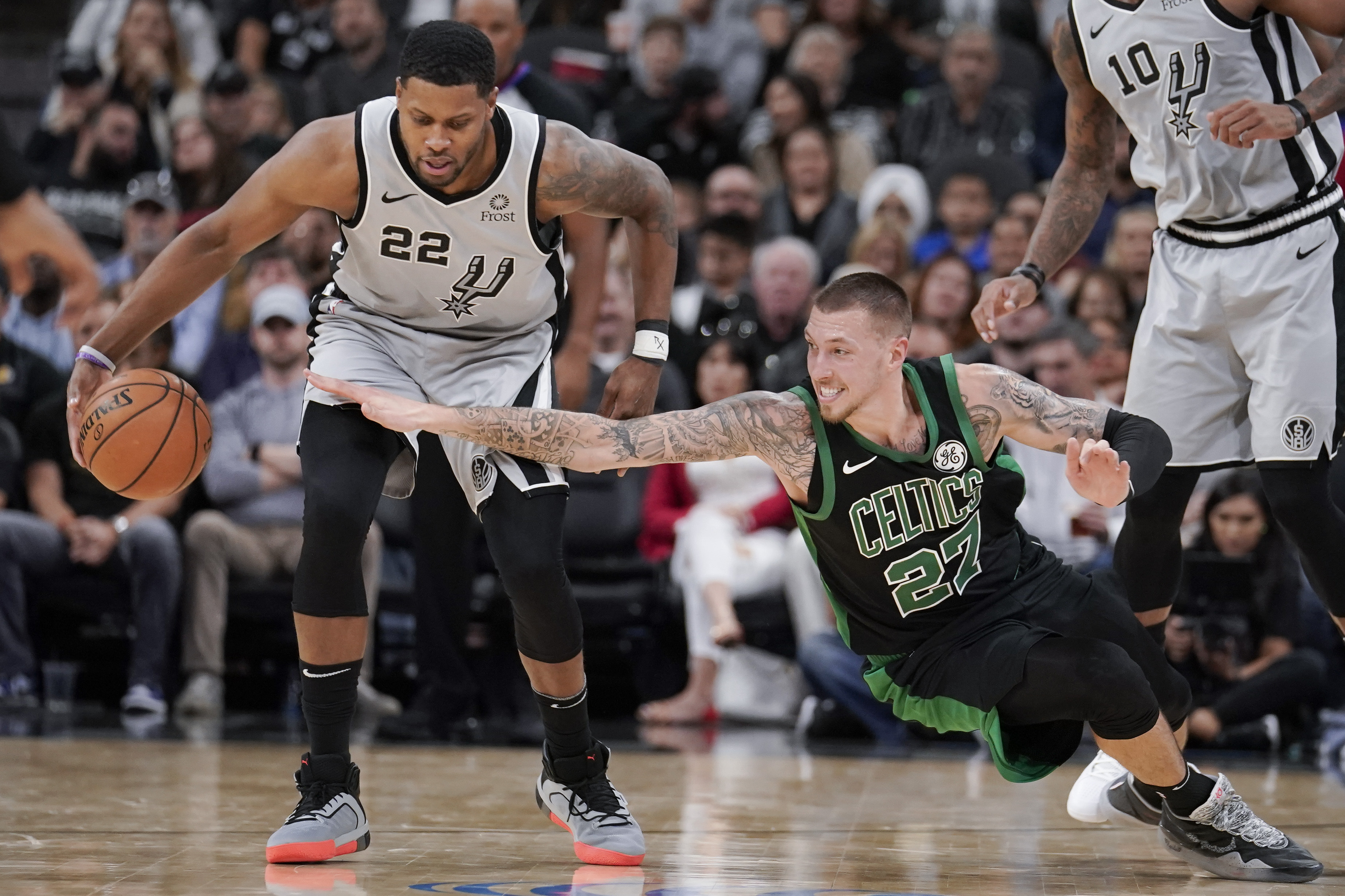 San Antonio Spurs' Rudy Gay (22) beats Boston Celtics' Daniel Theis for possession during the first half of an NBA basketball game, Saturday, Nov. 9, 2019, in San Antonio. (AP Photo/Darren Abate)