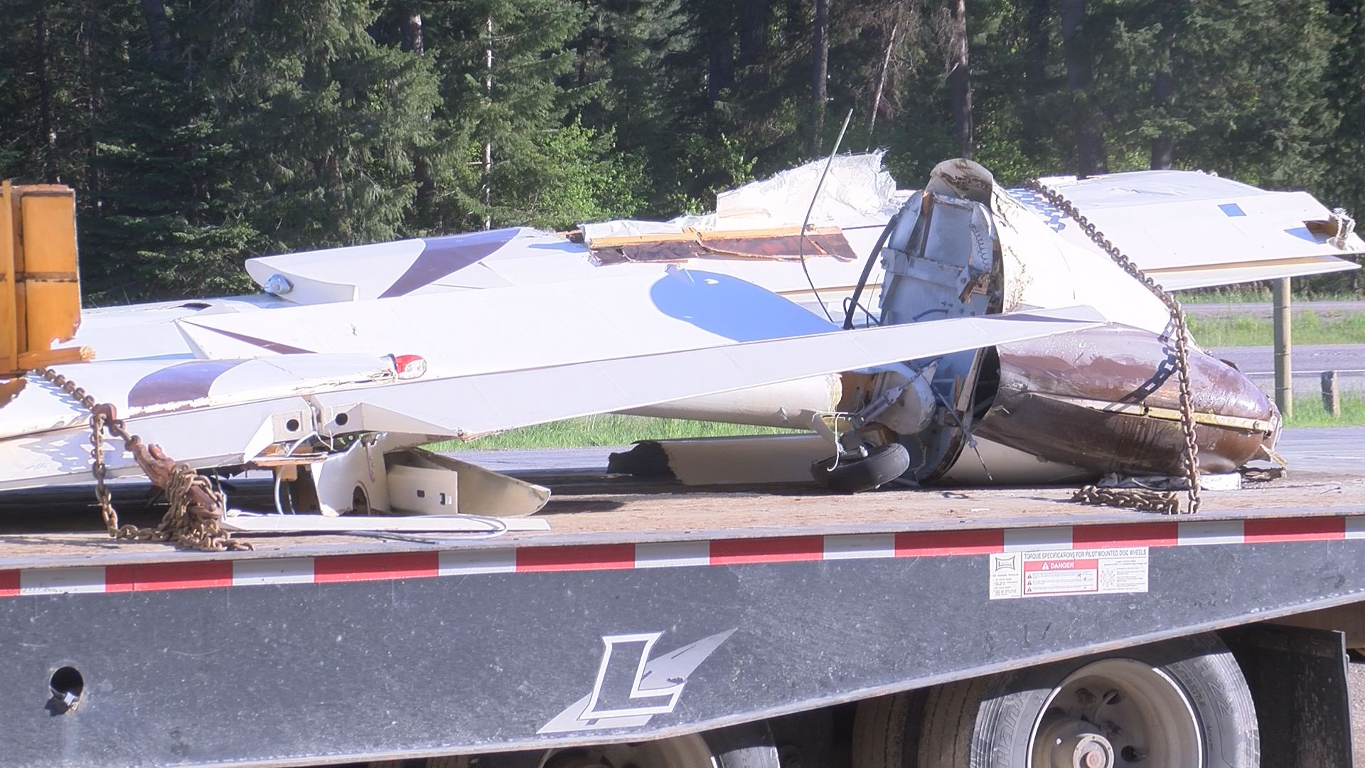 on the back of the flatbed truck is remnants of the experimental plane that crashed down on Interstate 90