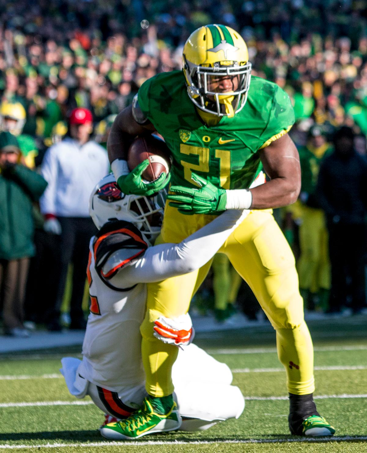 Oregon Ducks Royce Freeman struggles to get free from the Oregon State Beavers defender in the Civil War game in Autzen Stadium. At the half the Ducks led the Beavers 31 - 7. Photo by Katie Pietzold, Oregon News Lab