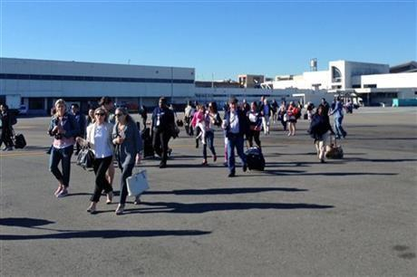 In this photo provided by John Forstrom, which has been authenticated based on its contents and other AP reporting, people walk across the tarmac after being evacuated from Los Angeles International Airport, Friday.