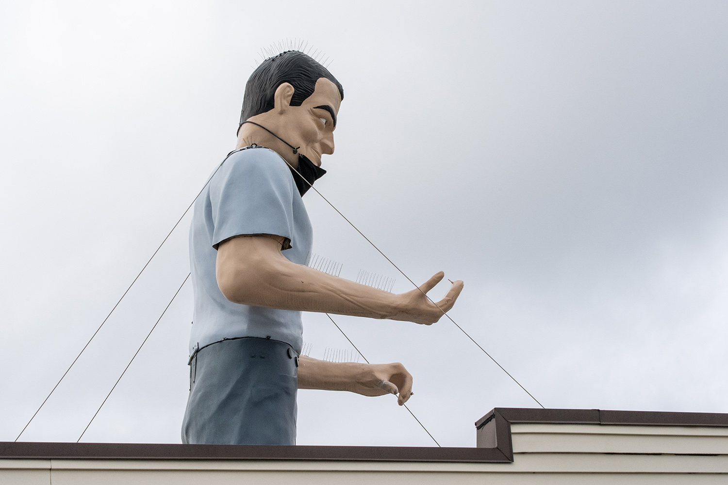 The Muffler Man used to hold a giant wrench, but reports say it went missing in the 1980s. Today, and specific to the pandemic, he's sporting a fancy face covering. (Rachael Jones / Seattle Refined)