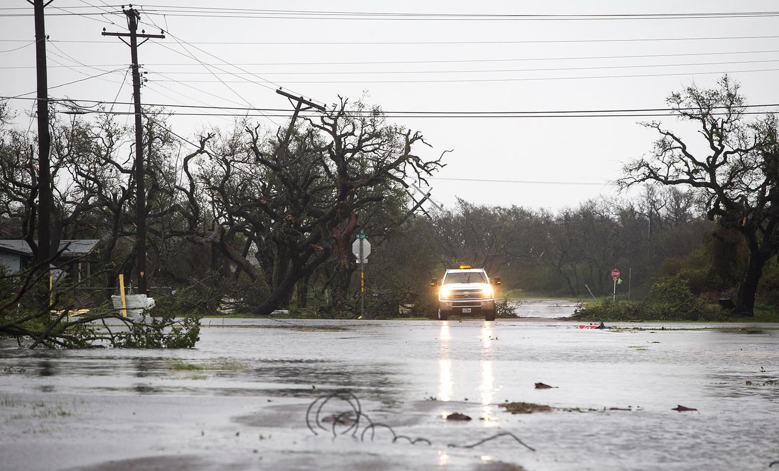 A vehicle drives through flooded roads after Hurricane Harvey ripped through Rockport, Texas, on Saturday, Aug. 26, 2017.  The fiercest hurricane to hit the U.S. in more than a decade spun across hundreds of miles of coastline where communities had prepared for life-threatening storm surges — walls of water rushing inland.  (Nick Wagner/Austin American-Statesman via AP)