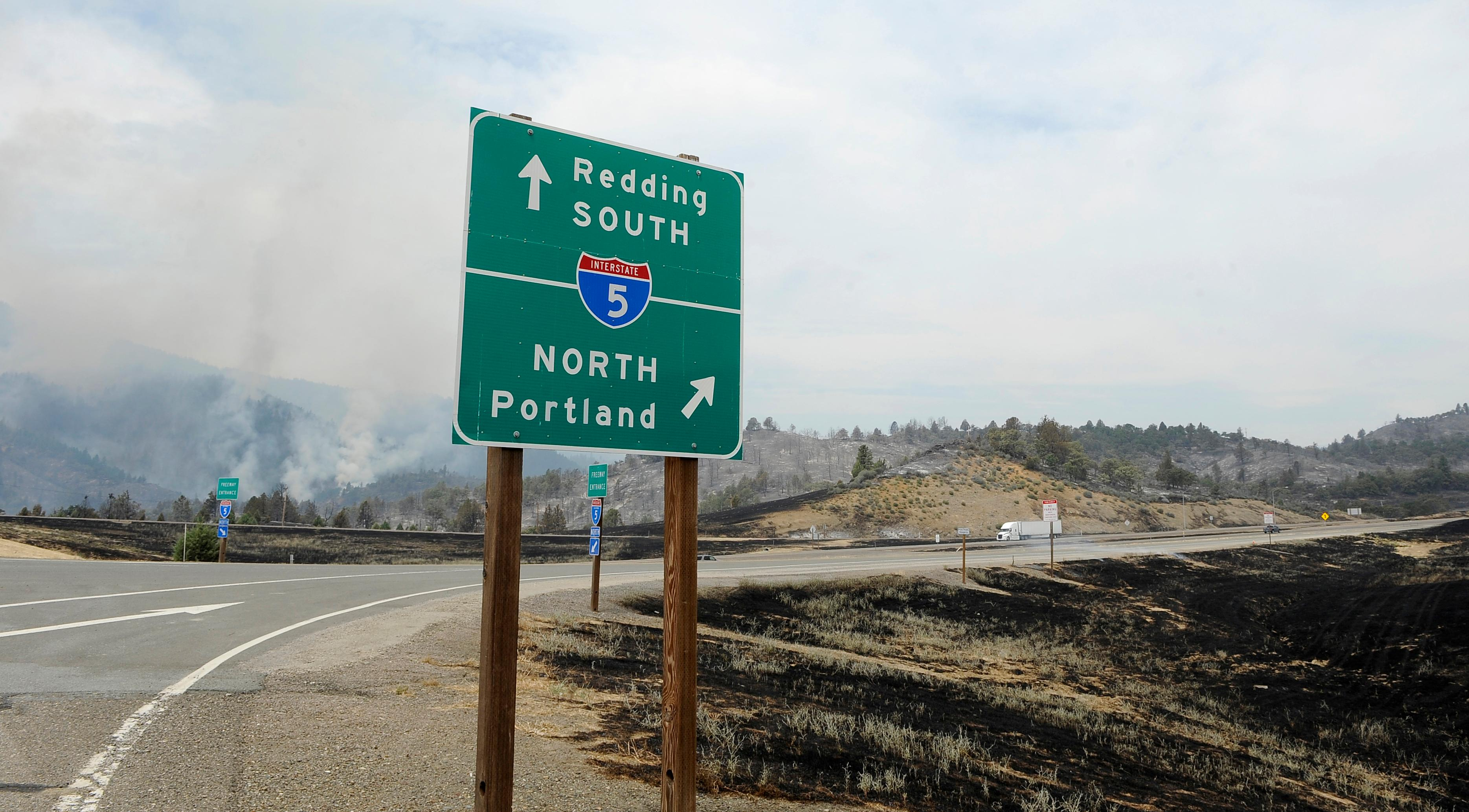 Andy Atkinson / Mail Tribune<br>A view from the Baily Hill Road freeway interchange shows the nearby hill still blazing south of the Oregon-California border Friday afternoon.