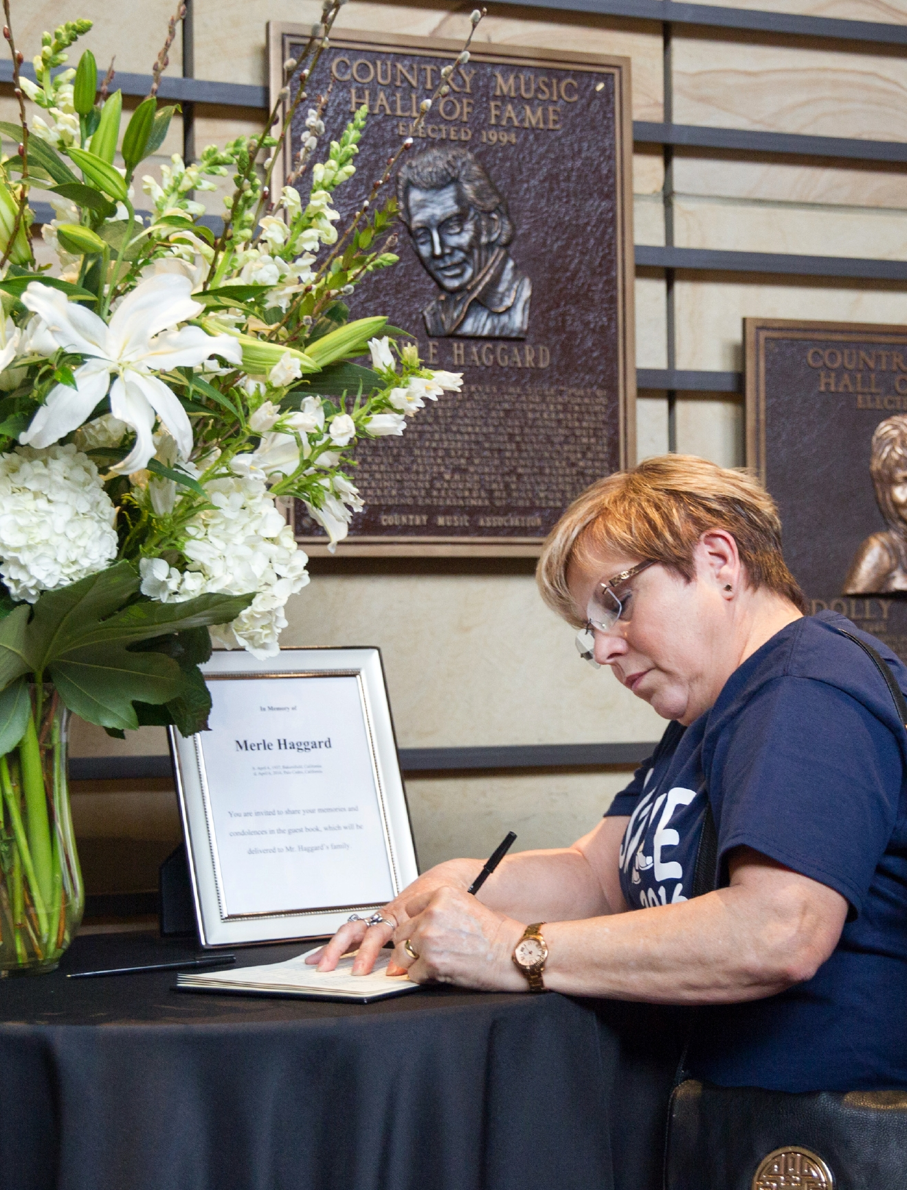 "Maggie Robichaux, of New Orleans, writes her condolences about the death of Merle Haggard at the Country Music Hall of Fame in Nashville, Tenn., Wednesday, April 6, 2016. Haggard, who rose from poverty and prison to international fame through his songs about outlaws, underdogs and an abiding sense of national pride in such hits as ""Okie From Muskogee"" and ""Sing Me Back Home,"" died Wednesday at 79, on his birthday.  (AP Photo/Erik Schelzig)"