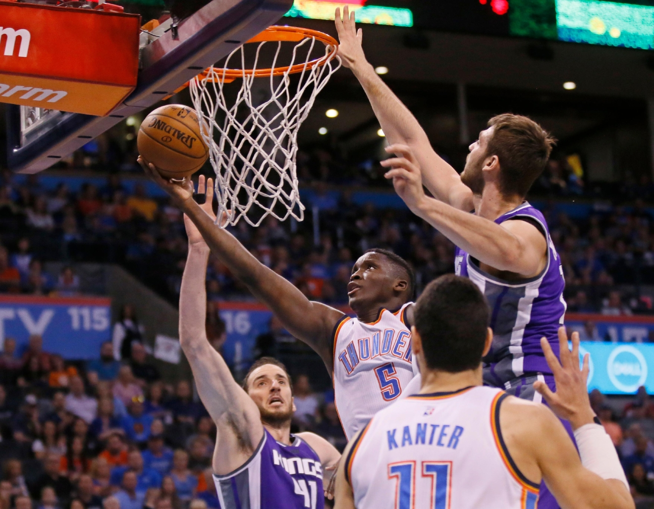 Oklahoma City Thunder guard Victor Oladipo (5) shoots between Sacramento Kings center Kosta Koufos (41) and center Georgios Papagiannis, right, in the second quarter of an NBA basketball game in Oklahoma City, Saturday, March 18, 2017. (AP Photo/Sue Ogrocki)