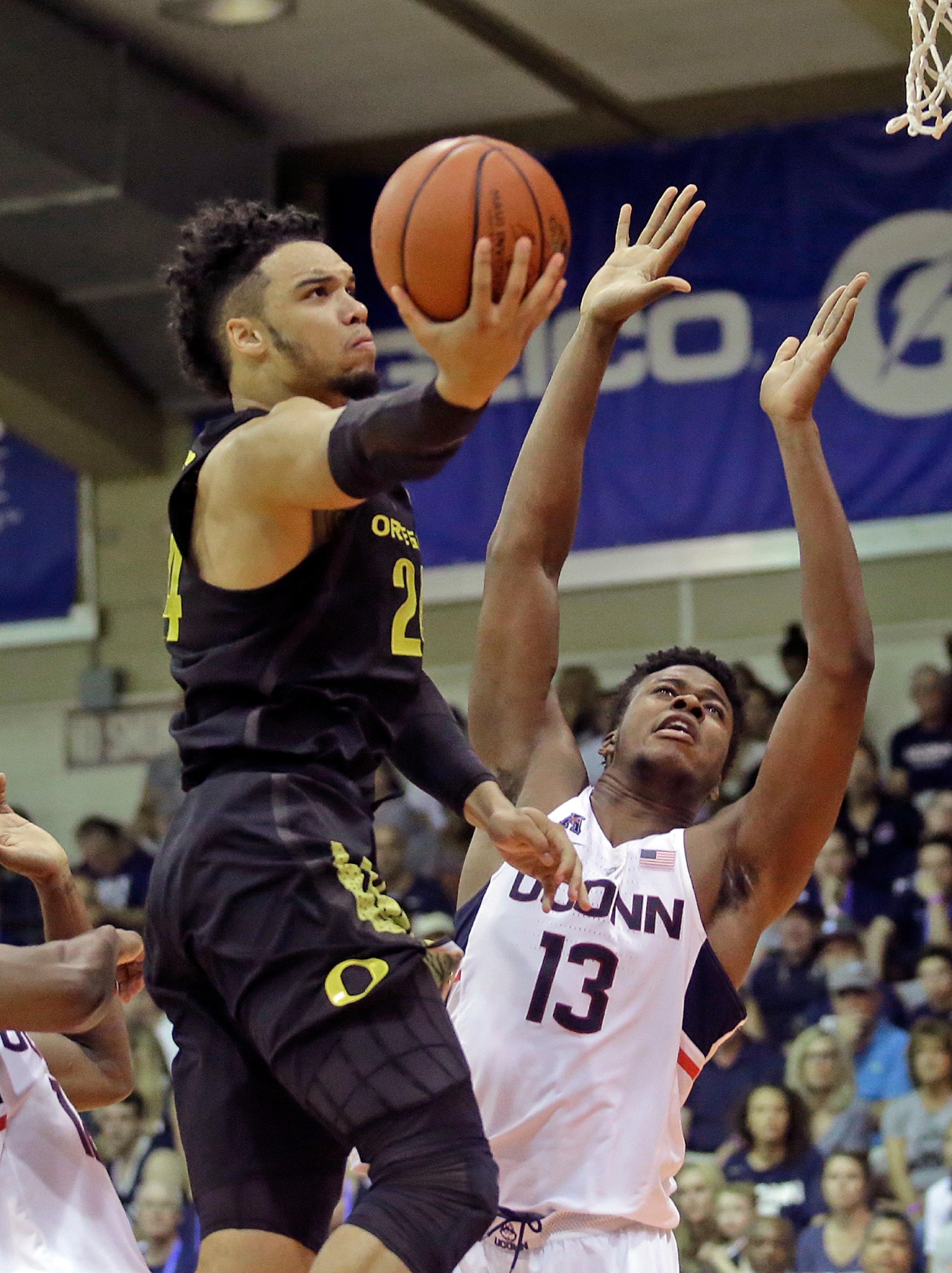 Oregon forward Dillon Brooks (24) goes to the basket as Connecticut forward Steven Enoch (13) defends in the first half during an NCAA college basketball game in the Maui Invitational, Wednesday, Nov. 23, 2016, in Lahaina, Hawaii. (AP Photo/Rick Bowmer)