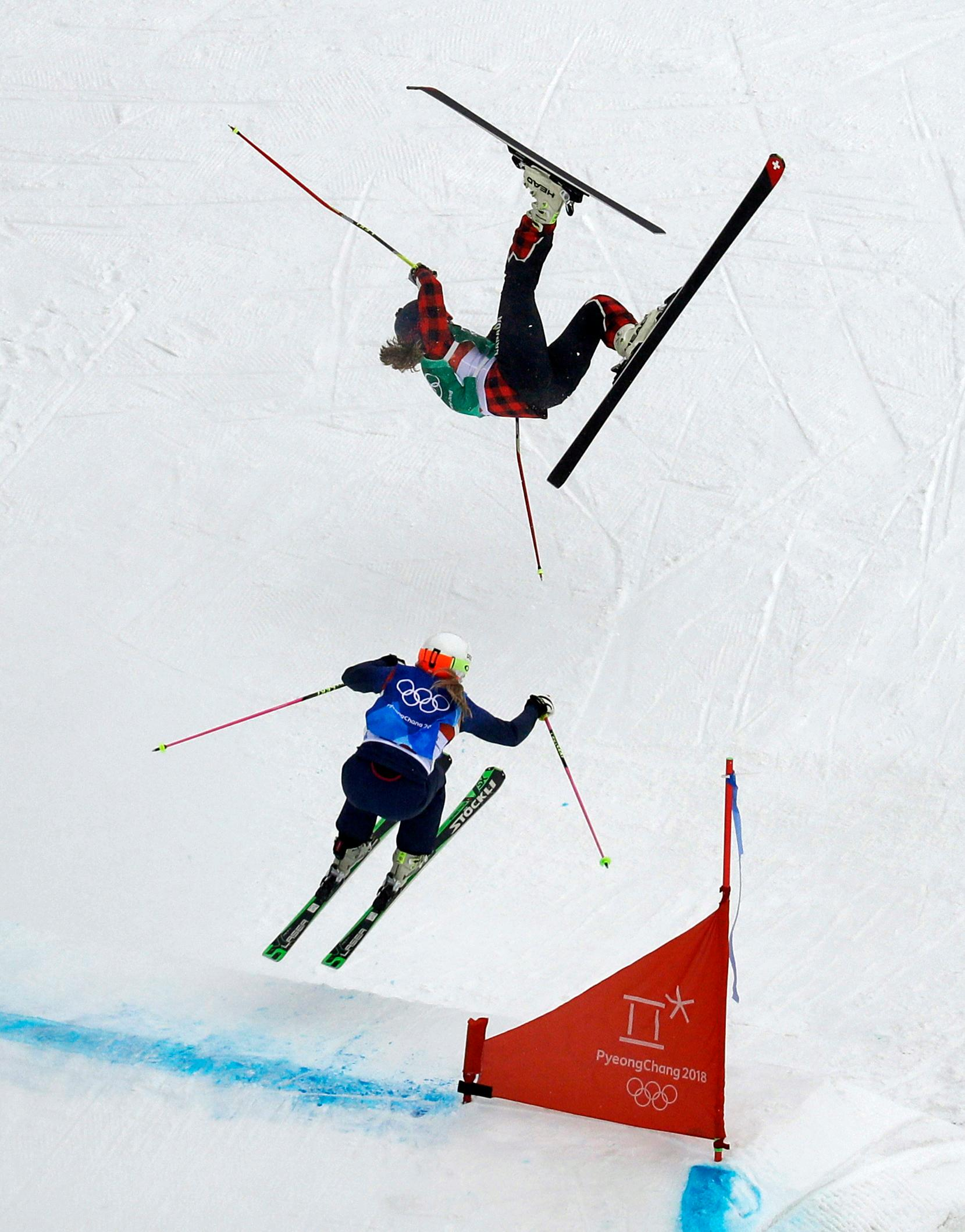 India Sherret, of Canada, crashes as Emily Sarsfield, of Britain, jumps during the women's ski cross elimination round at Phoenix Snow Park at the 2018 Winter Olympics in Pyeongchang, South Korea, Friday, Feb. 23, 2018. (AP Photo/Kin Cheung)