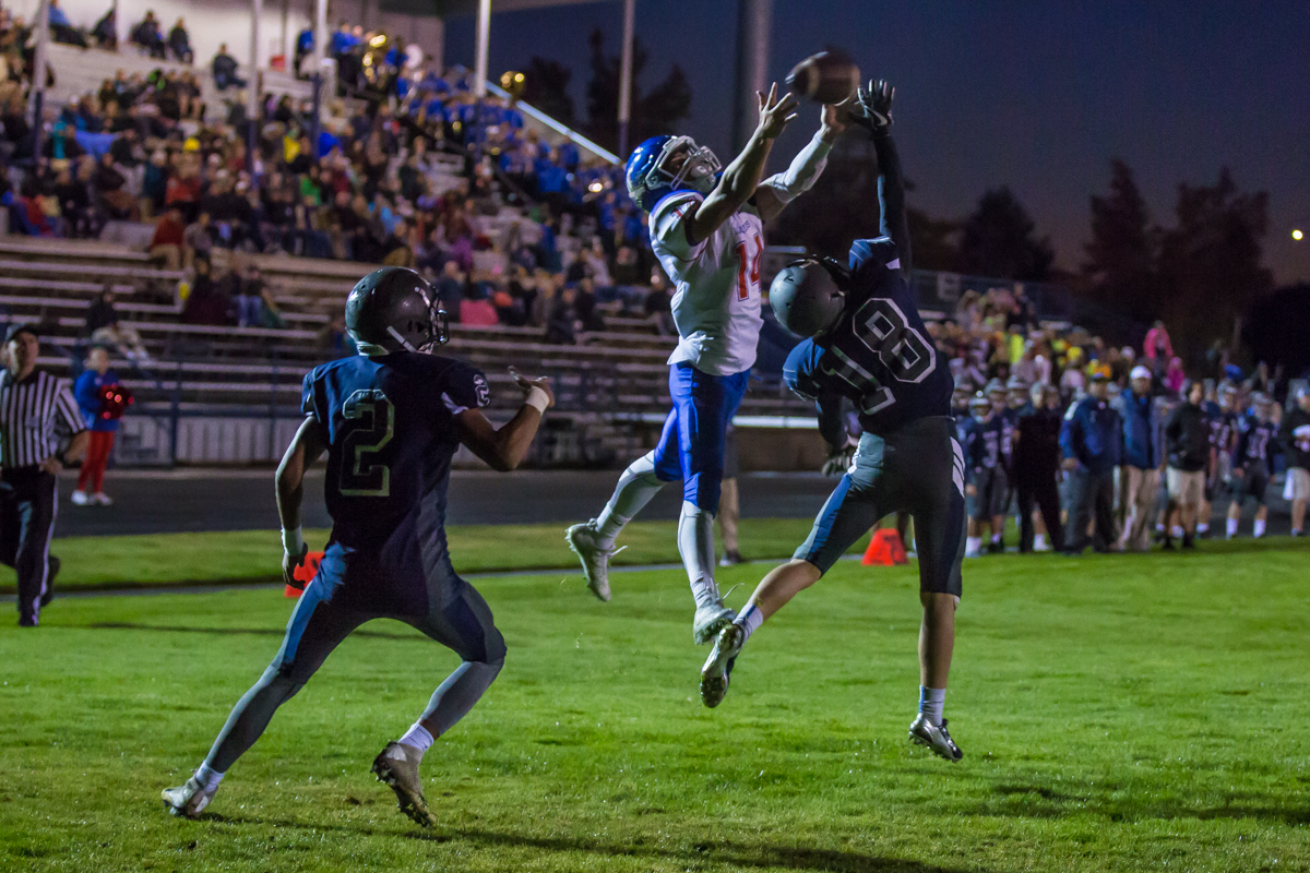 Churchill receiver Myles Green-Richards (#14) leaps over two Springfield defenders to score a touchdown. The Churchill Lancers defeated the Springfield Millers 56-7 in a cold game Friday night. Friday night's win extended Churchill's season to 7-0. Photo by Dillon Vibes
