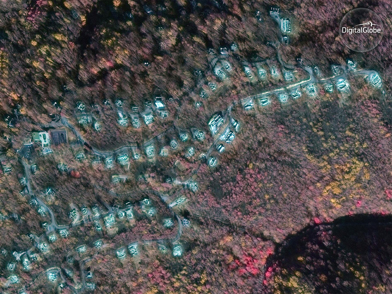 This Dec. 1, 2016, satellite image using near-infrared (NIR) provided by DigitalGlobe shows damage from the wildfire near Ripley's Aquarium of the Smokies in Gatlinburg, Tenn. NIR imagery causes healthy vegetation to appear red and the burn scar from the wildfire to be dark brown. More than 14,000 residents and visitors in Gatlinburg were forced to evacuate, and the typically bustling tourist city has been shuttered ever since. (Digital Globe via AP)