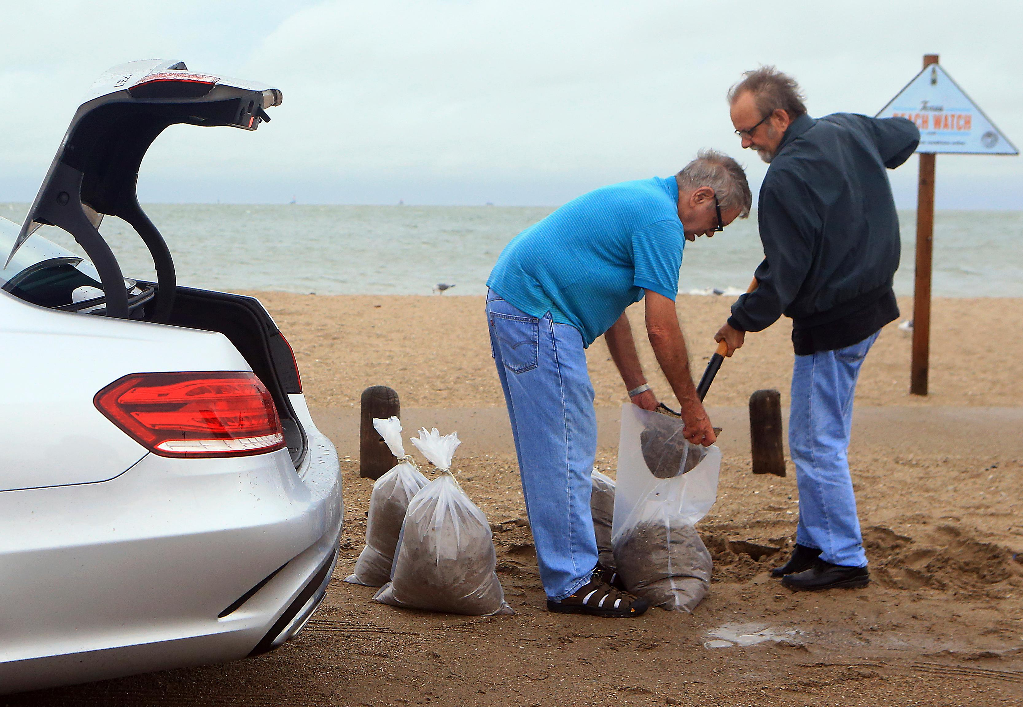 Tom Corbin, right, and Terry Corbin prepare sandbags as Hurricane Harvey approaches the Coastal Bend area on Friday, Aug. 25, 2017, in Corpus Christi, Texas. The National Hurricane Center warns that conditions are deteriorating as Hurricane Harvey strengthens and slowly moves toward the Texas coast. (Gabe Hernandez/Corpus Christi Caller-Times via AP)