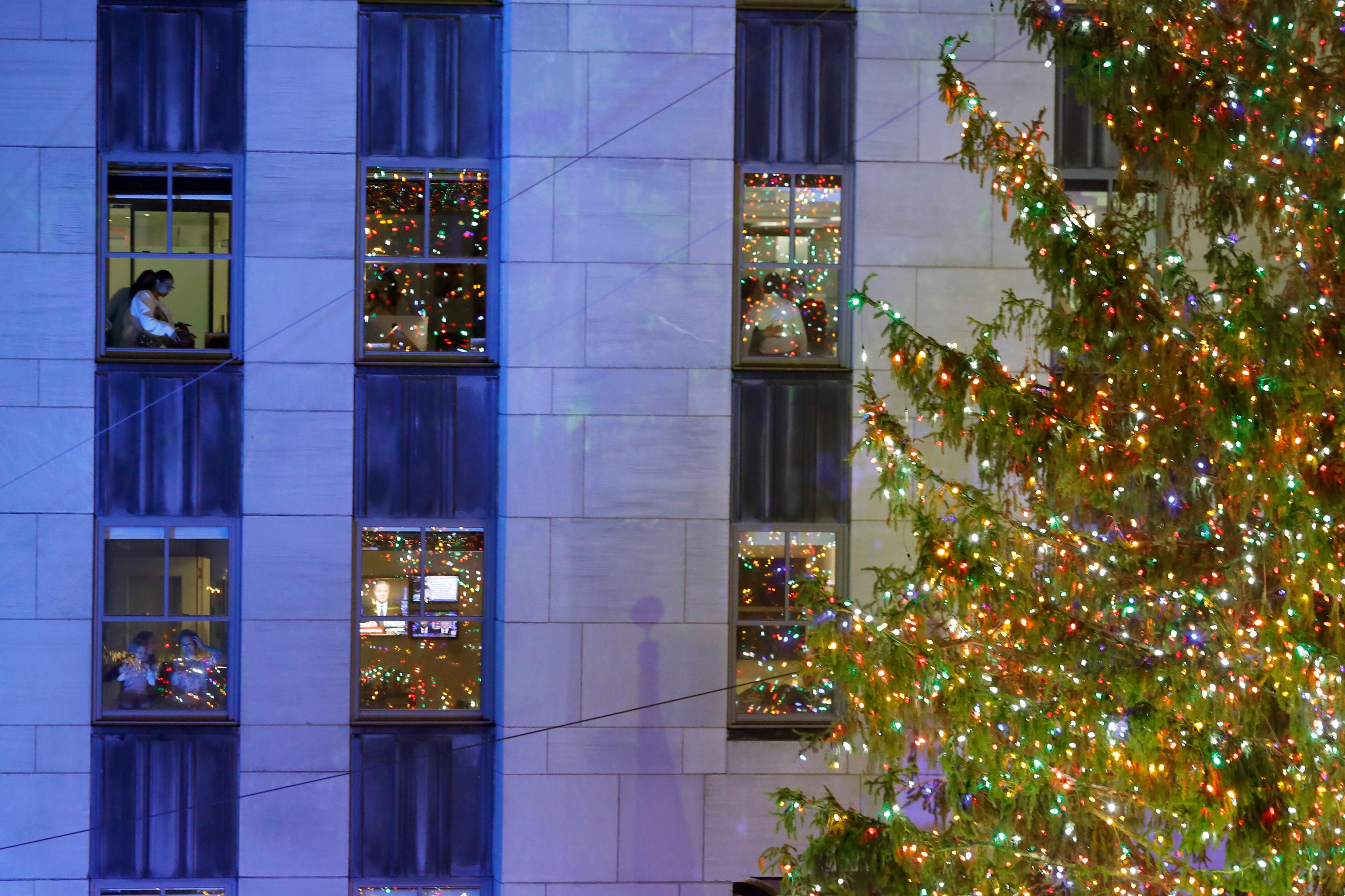 Workers are seen in a window moments after 87th annual Rockefeller Center Christmas Tree was illuminated, Wednesday, Dec. 4, 2019, in New York. (AP Photo/Kathy Willens)