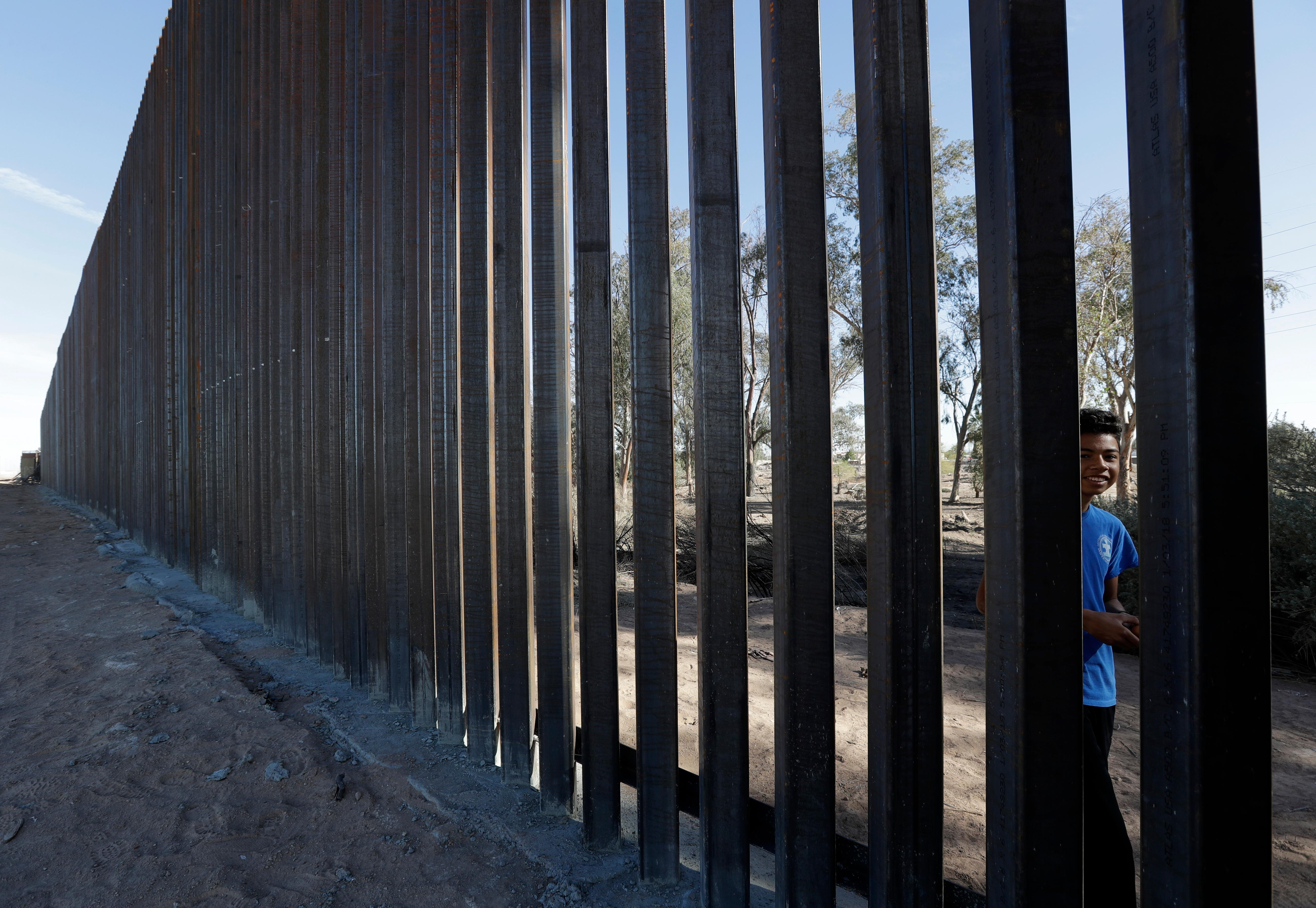 In this March 5, 2018, photo, a boy looks through the first section of a newly-constructed structure along the border separating Mexicali, Mexico, right, and Calexico, Calif. As Donald Trump prepares for his first visit to the U.S.-Mexico border as president, little has changed despite the heated rhetoric. (AP Photo/Gregory Bull)