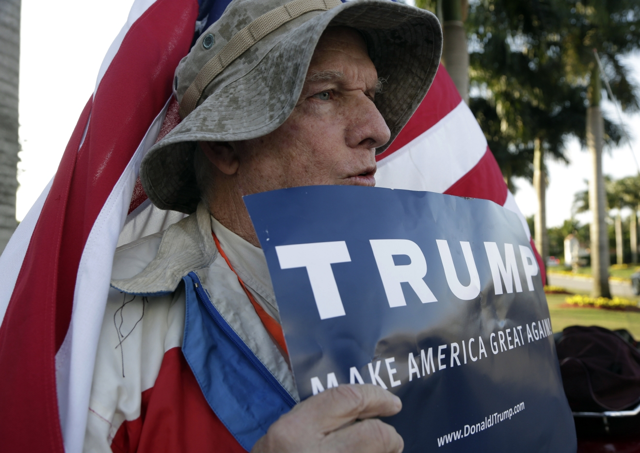 John King, 74, of Miami, holds a sign supporting Republican presidential candidate Donald Trump outside of the Trump National Doral golf resort, as opponents to Trump protest across the street,  Monday, March 14, 2016, in Doral, Fla. Voters go to the polls in Florida Tuesday for the primary election. (AP Photo/Lynne Sladky)