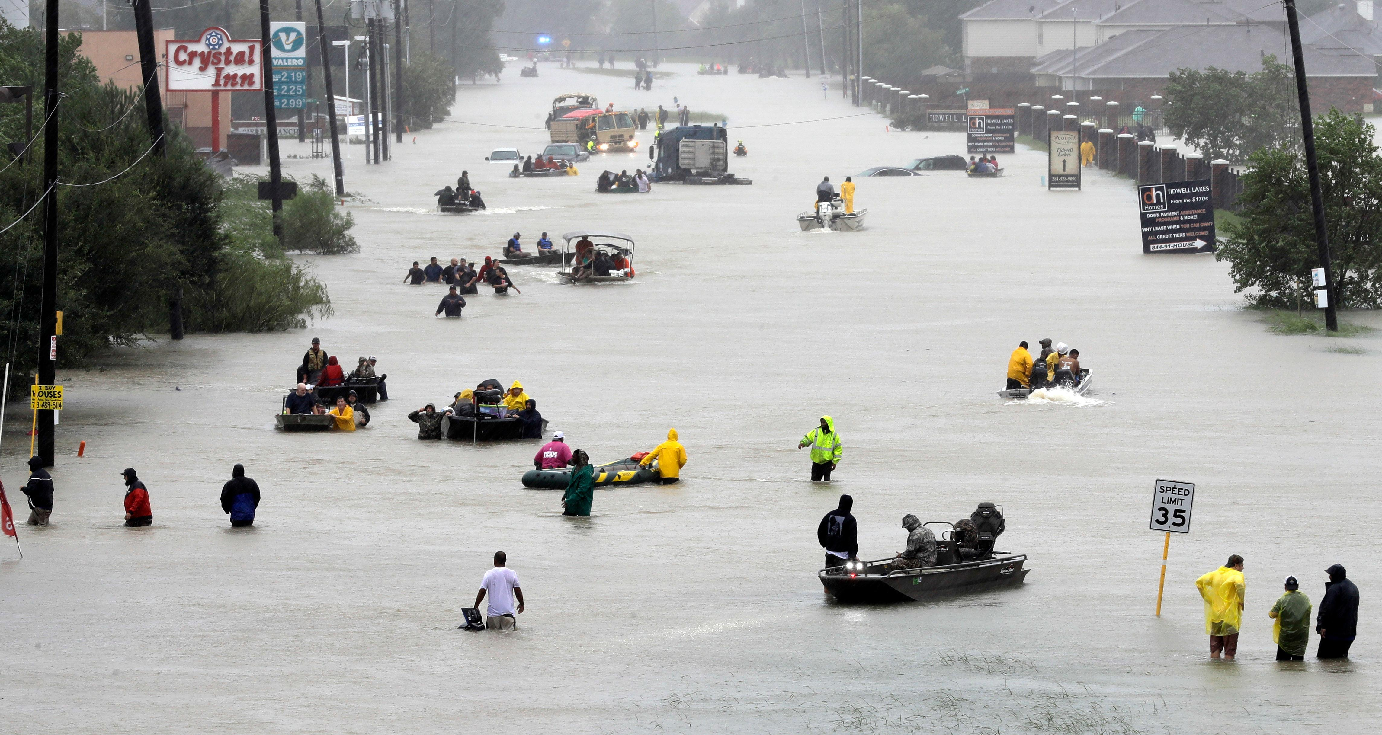 Rescue boats fill a flooded street as flood victims are evacuated as floodwaters from Tropical Storm Harvey rise Monday, Aug. 28