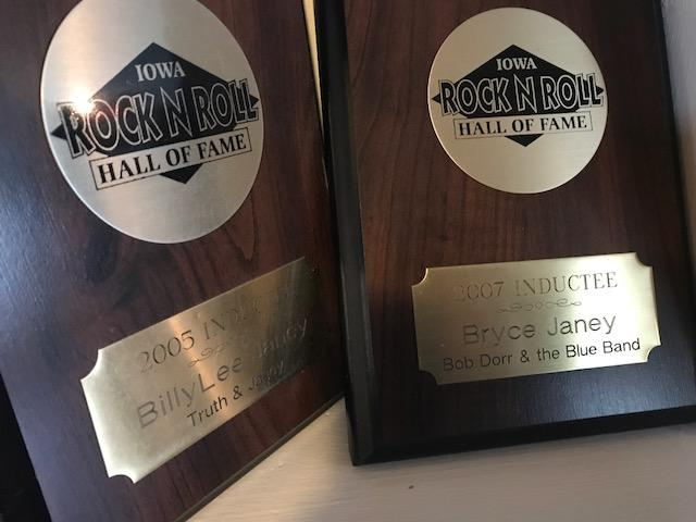 Award plaques representing Bryce Janey's and Billy Lee Janey's separate inductions into the Iowa Rock 'n Roll Music Association Hall of Fame.