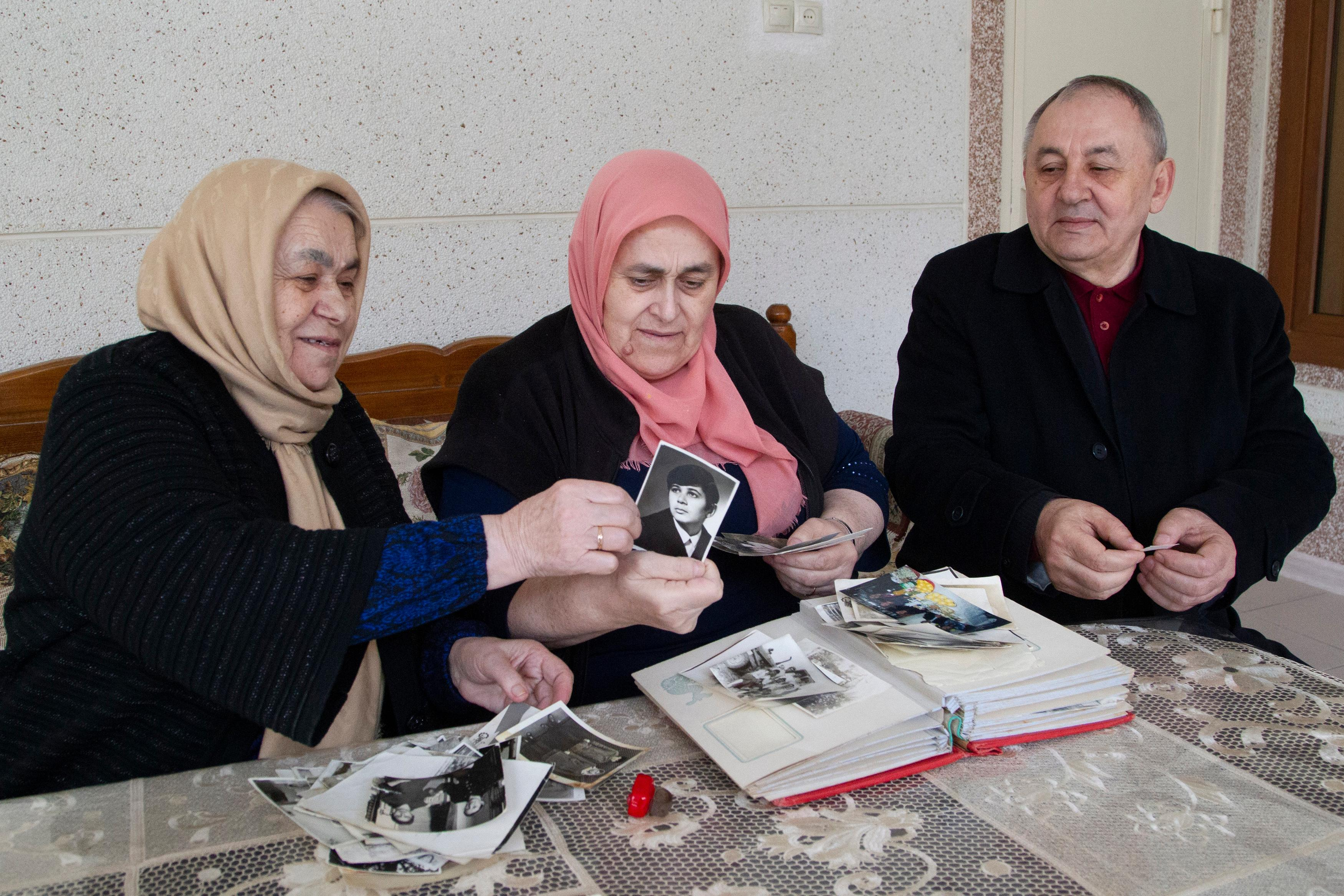 In this Sunday, March 17, 2019, photo, Zharadat Titiyeva, left, Khava Zakriyeva, center, and Yakub Titiyev look through the family pictures that feature their sibling, jailed activist Oyub Titiyev, at their family home in Kurchaloy, Chechnya, Russia.{ } (AP Photo/Musa Sadulayev)