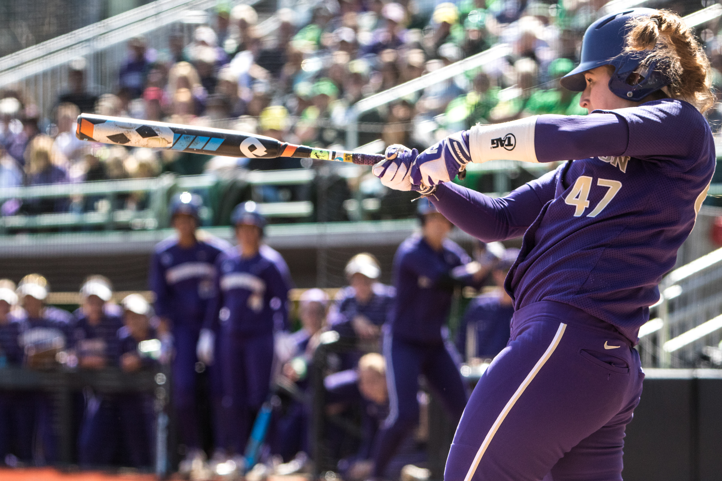 Washington Huskies catcher Morganne Flores (#47) completes her swing on her second two-run double during the ninth inning. In the final game of a three-game series, the University of Washington Huskies defeated the Oregon Ducks 5-3.  The Ducks led through the bottom of the 7th inning, but Washington's Morganne Flores (#47) tied it up with a two-run double.  Flores drove in two more runs in the 9th to take the lead.  Photo by Austin Hicks, Oregon News Lab