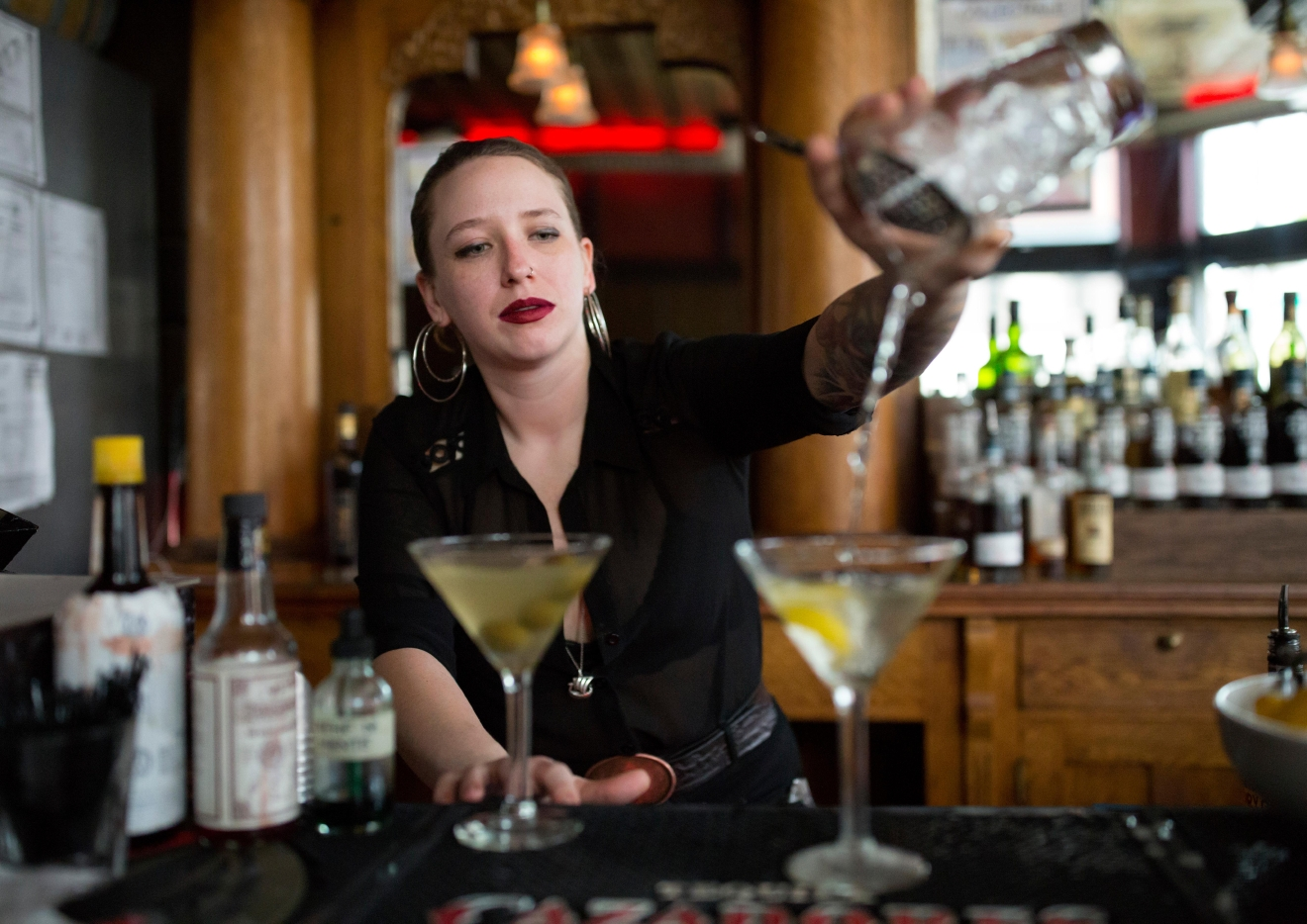 Meghan West, who has only been bartending at Tini Bigs Lounge for a year, pours martinis during the bar's final day of business. (Sy Bean / Seattle Refined)
