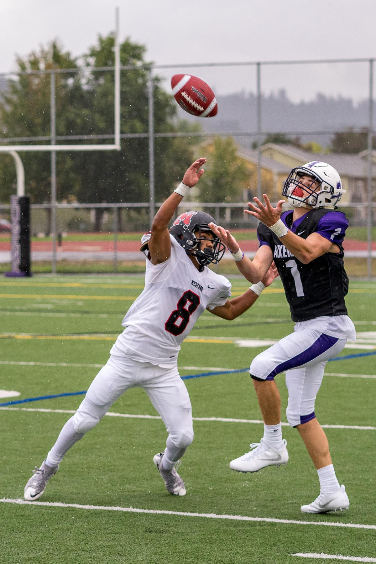 South Eugene's Elliot James (#1) and North Medford's Vicente Borja (#8) compete for a reception. North Medford defeated South Eugene 27 – 8 on Monday afternoon at South Eugene High School. The game had been rescheduled due to unhealthy levels of smoke in the air caused by nearby forest fires. Photo by Kit MacAvoy, Oregon News Lab