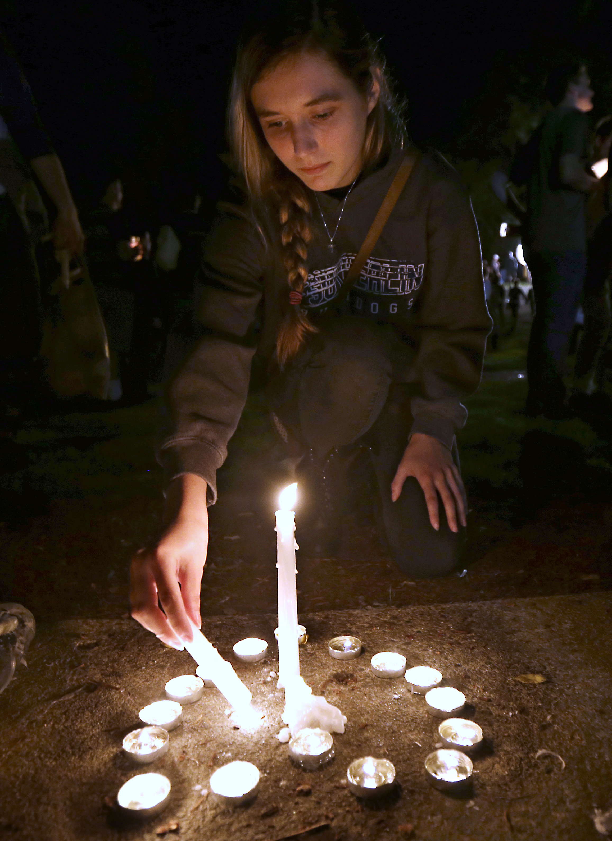 Mykyla Shaw lights a candle during a vigil for those killed in a shooting at Umpqua Community College, Thursday, Oct. 1, 2015, in Roseburg, Ore. (AP Photo/Rich Pedroncelli)