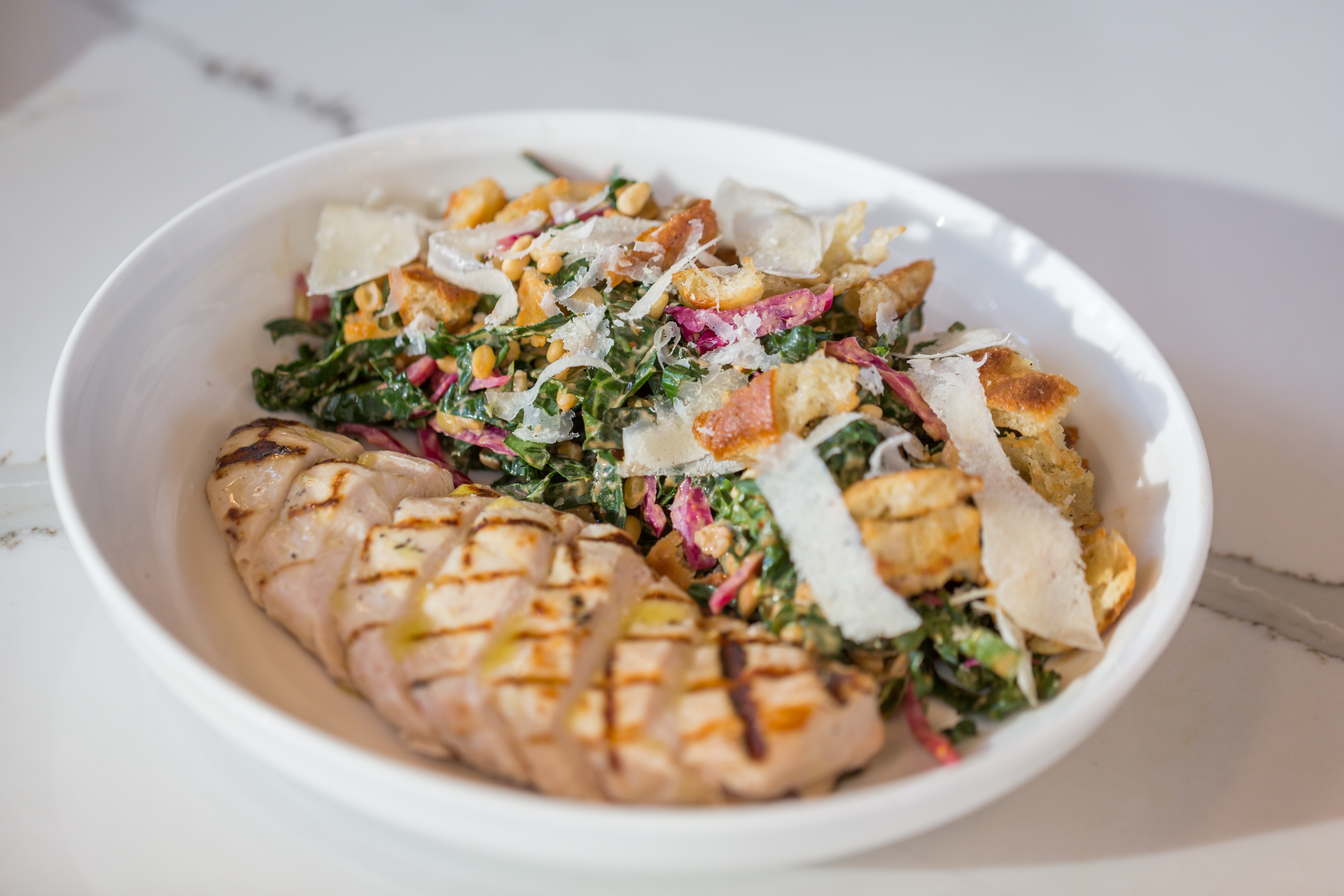 <p>Tuscan Kale Salad: pickled cabbage, charred corn, cotija and lime vinaigrette (Image: Courtesy District Winery)</p>