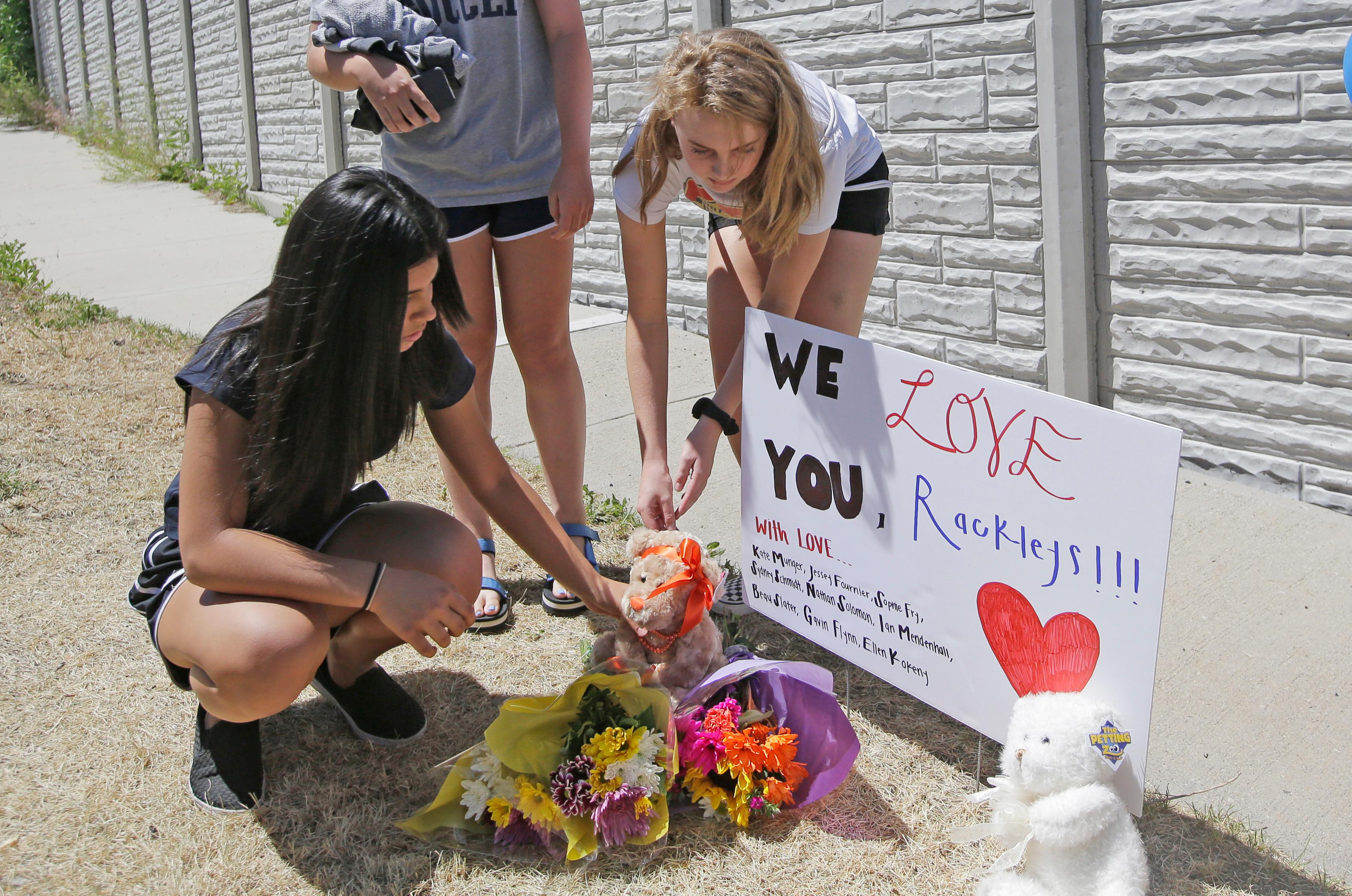 People leave items at a memorial for the victims of a fatal shooting Wednesday, June 7, 2017, in Sandy, Utah. Utah investigators and residents of a middle-class Salt Lake City suburb were trying Wednesday to understand what led a man to open fire on a woman and children inside a car leaving the woman and one of her sons dead, another son in critical condition and a girl injured. The suspect was found dead of a self-inflicted gunshot wound at the scene in a quiet neighborhood of the city of Sandy. (AP Photo/Rick Bowmer)