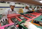 In this May 26, 2010 file photo, staff members work on the production line at the Foxconn complex in the southern Chinese city of Shenzhen, Southern city in China.