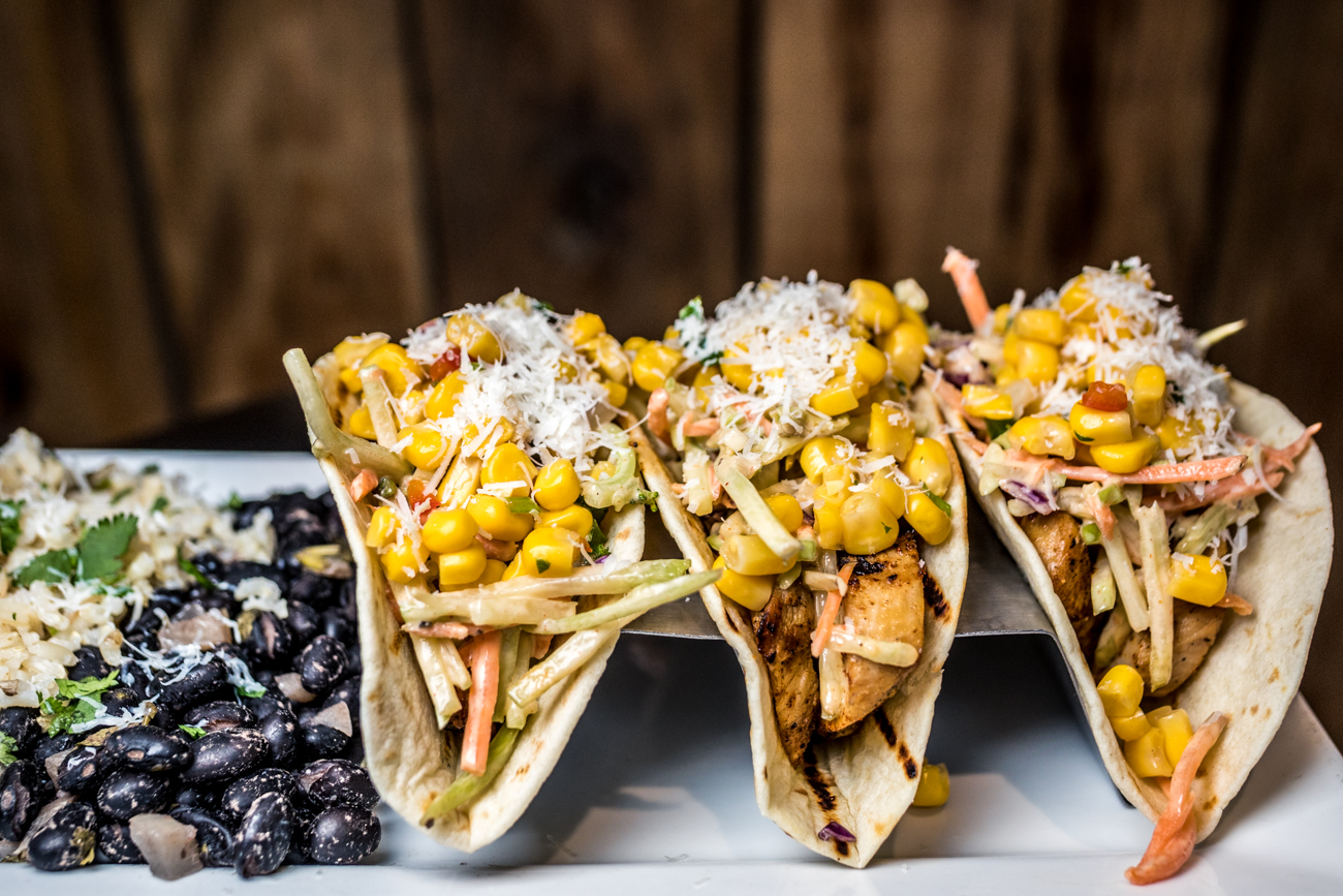 Chicken Tacos: three tacos stuffed with chicken, fire-roasted corn salsa, shredded cabbage, cotija cheese, and chipotle dressing served with a side of black beans and rice / Image: Catherine Viox // Published: 3.7.20