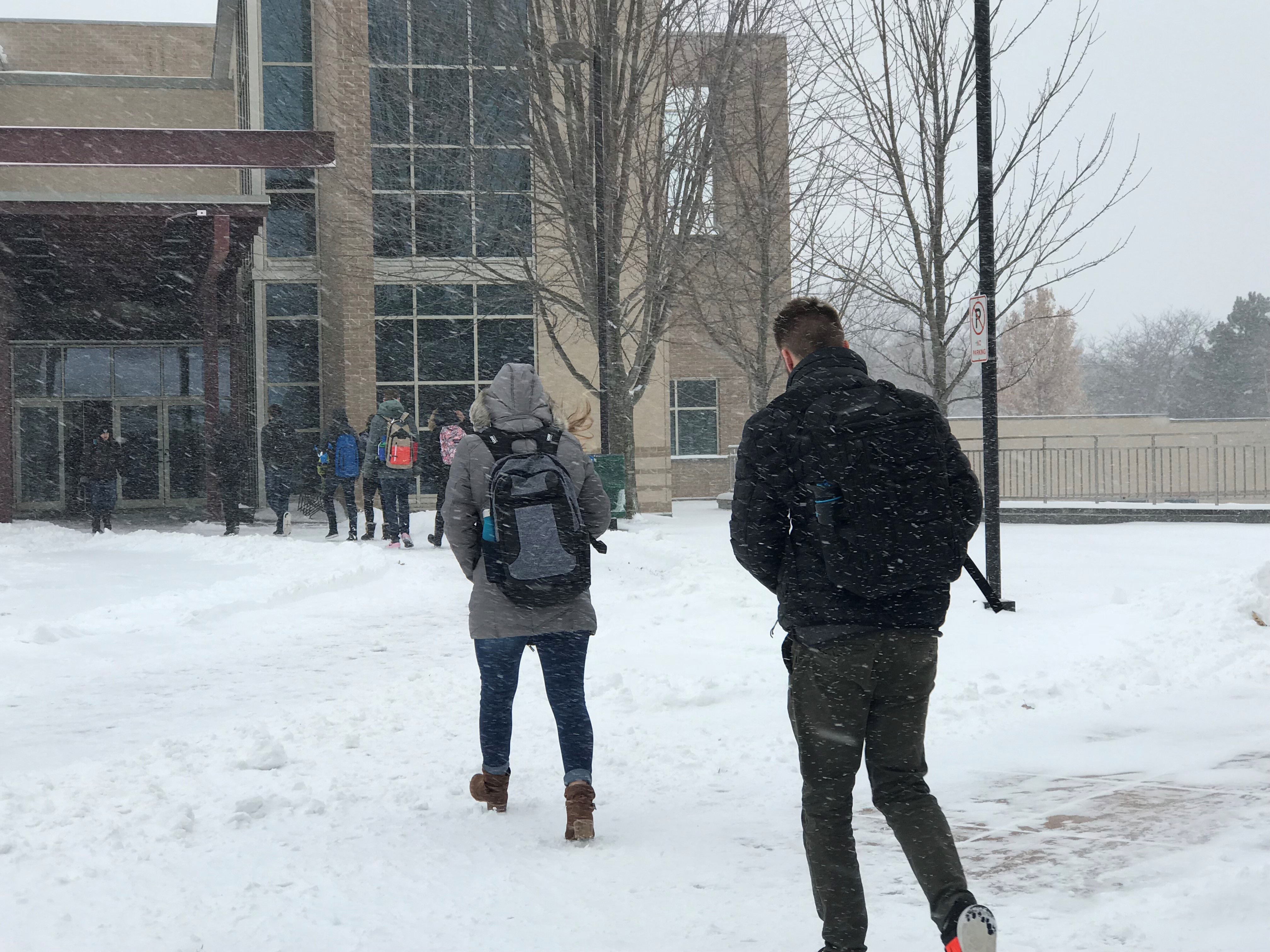 University of Wisconsin-Green Bay students walk on a snowy campus Dec. 13, 2017, during Winter Storm Abigail. (WLUK/Gabrielle Mays)