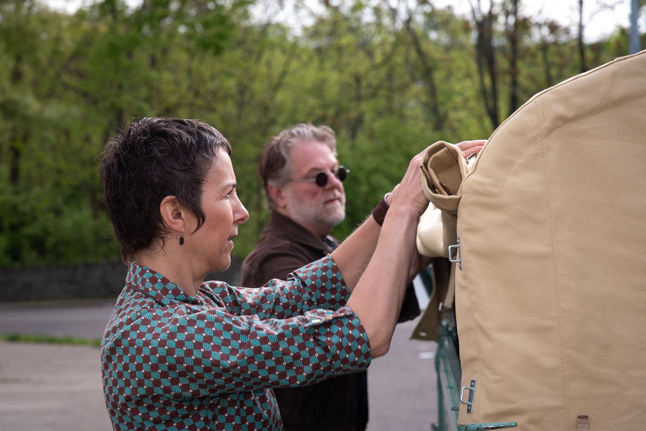 Melanie and Tony roll up the canvas cover of the truck to set up the books / Image: Phil Armstrong, Cincinnati Refined // Published: 5.20.19