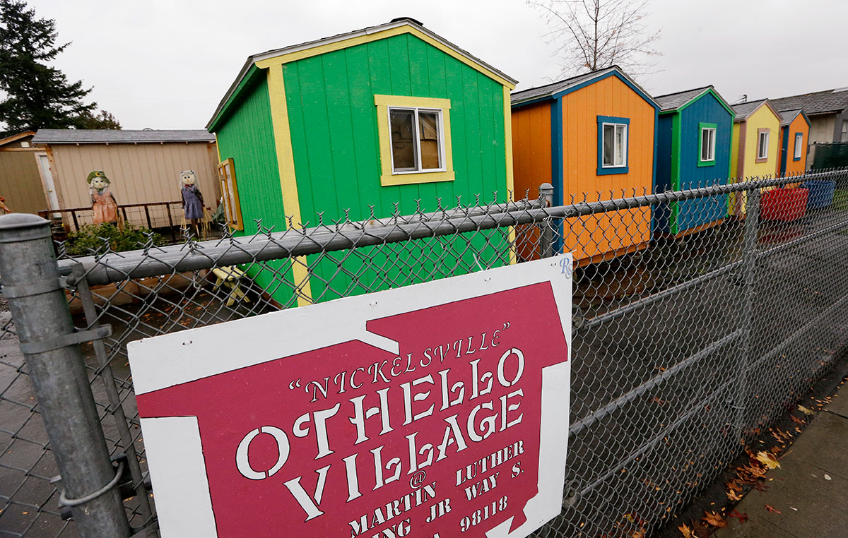 FILE - In this Thursday, Nov. 9, 2017, file photo, a line of tiny houses stand with their backs to the adjacent street at a homeless encampment in Seattle. In the absence of legislation to incentivize the acceptance of Section 8 vouchers, politicians and advocates have been scrambling to keep up with the surge of unsheltered residents in the state. One answer in Seattle has been the so-called tiny houses, portable 120-square-foot shacks of simple wood construction, which now include seven villages with a capacity to house 350 people since its start in 2015. (AP Photo/Elaine Thompson, File)